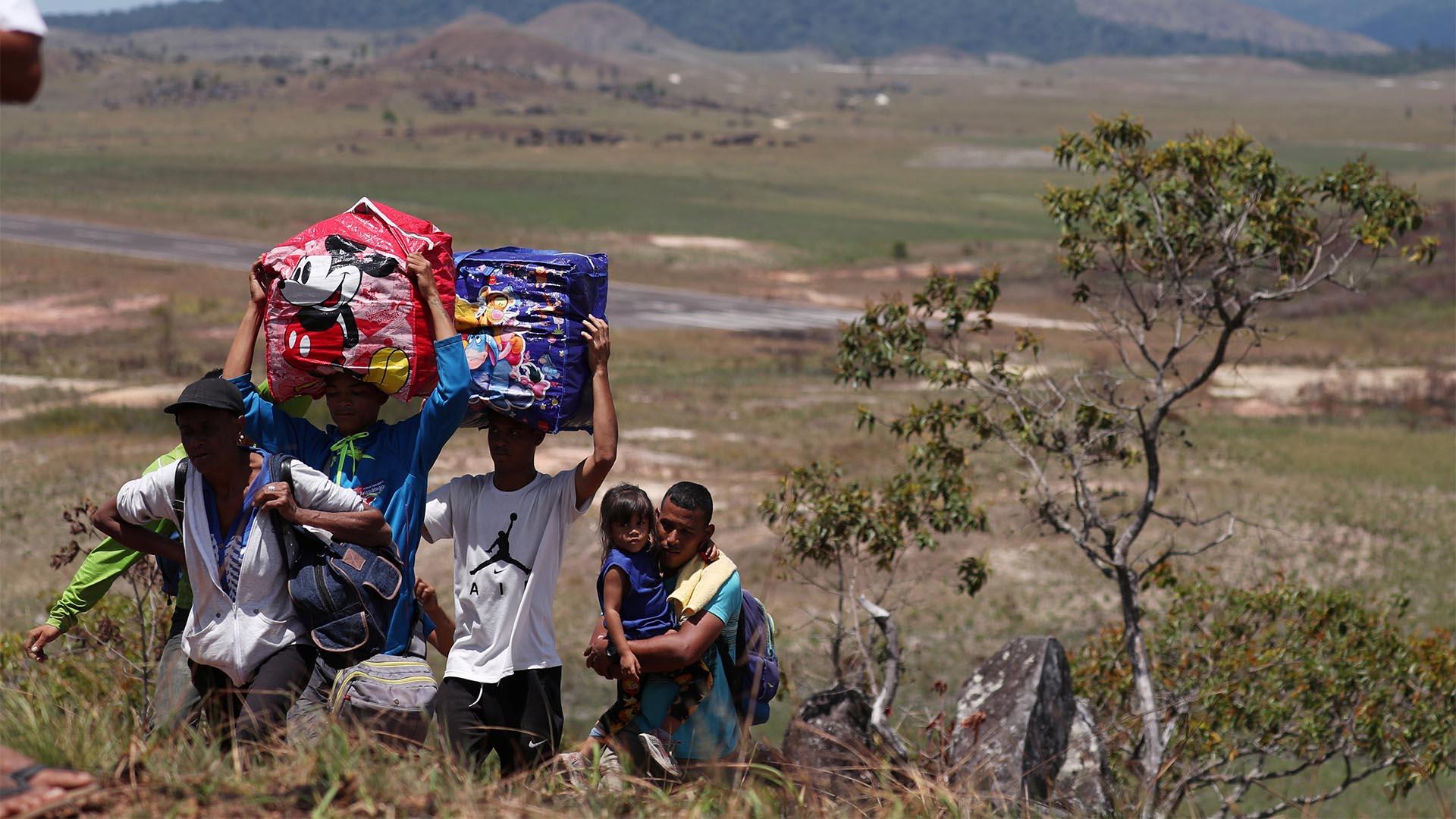 La gente camina con sus pertenencias a través de un campo, mientras intenta cruzar la frontera entre Venezuela y Brasil en Pacaraima, estado de Roraima (Reuters)