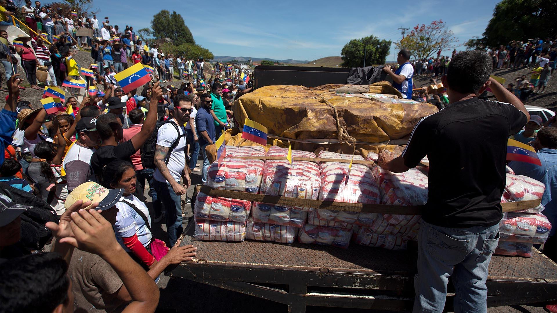 Personas celebran este sábado la llegada de la primera de las dos grandes camionetas cargadas con parte de la ayuda humanitaria de Brasil para Venezuela a la localidad Pacaraima, en el límite fronterizo entre ambos países (EFE)