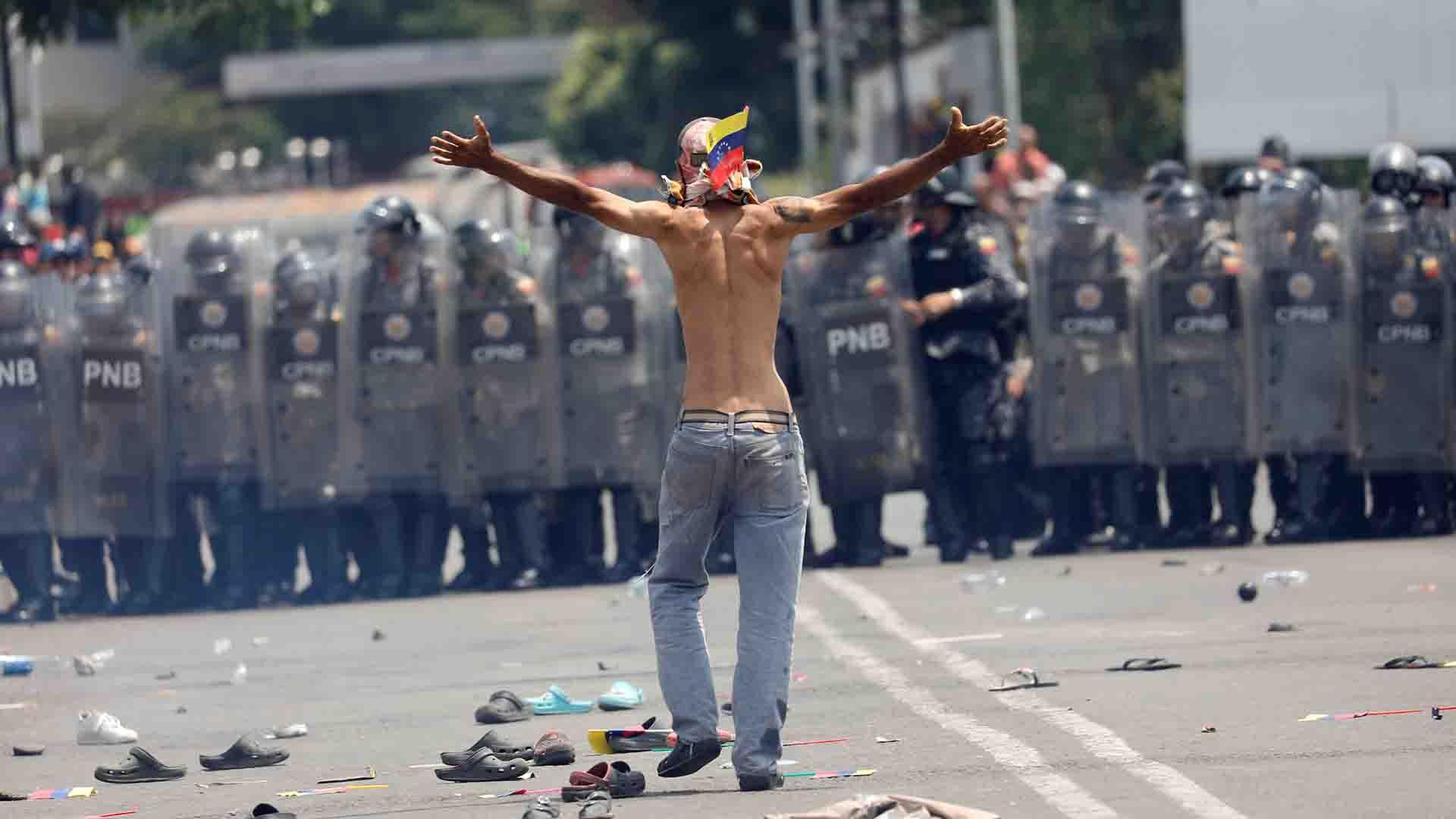 Un manifestante de la oposición venezolana hace un gesto hacia las fuerzas de seguridad de Venezuela en el puente Simón Bolívar en la frontera entre Colombia y Venezuela, visto desde Cúcuta (Reuters)