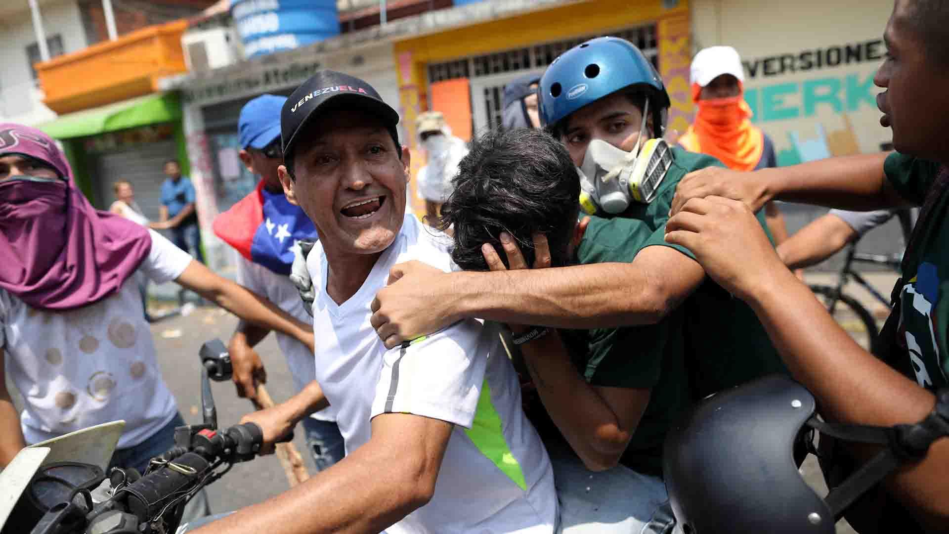 Un manifestante es asistido por otros tras la represión en Ureña, frontera con Colombia (Reuters)