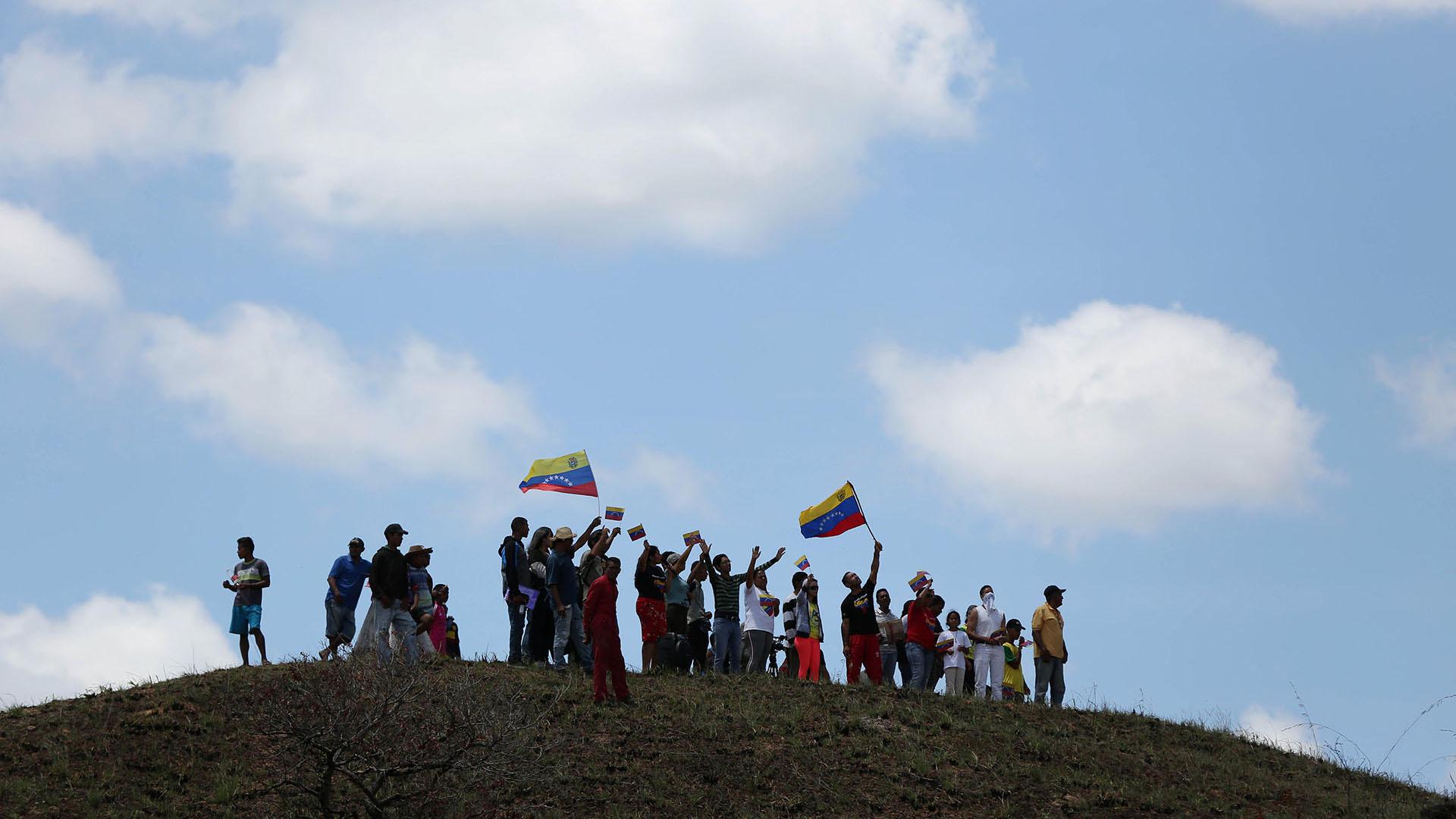 La gente saluda a un camión que lleva ayuda humanitaria mientras cruza a Venezuela desde Brasil (Reuters)