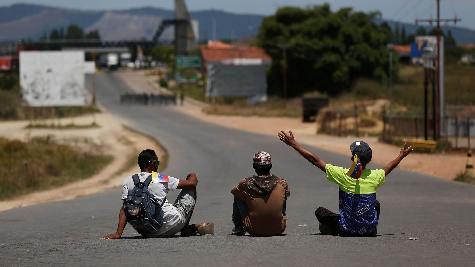 Hombres sentados en el camino de un camión que lleva ayuda humanitaria a Venezuela desde Brasil (Reuters)