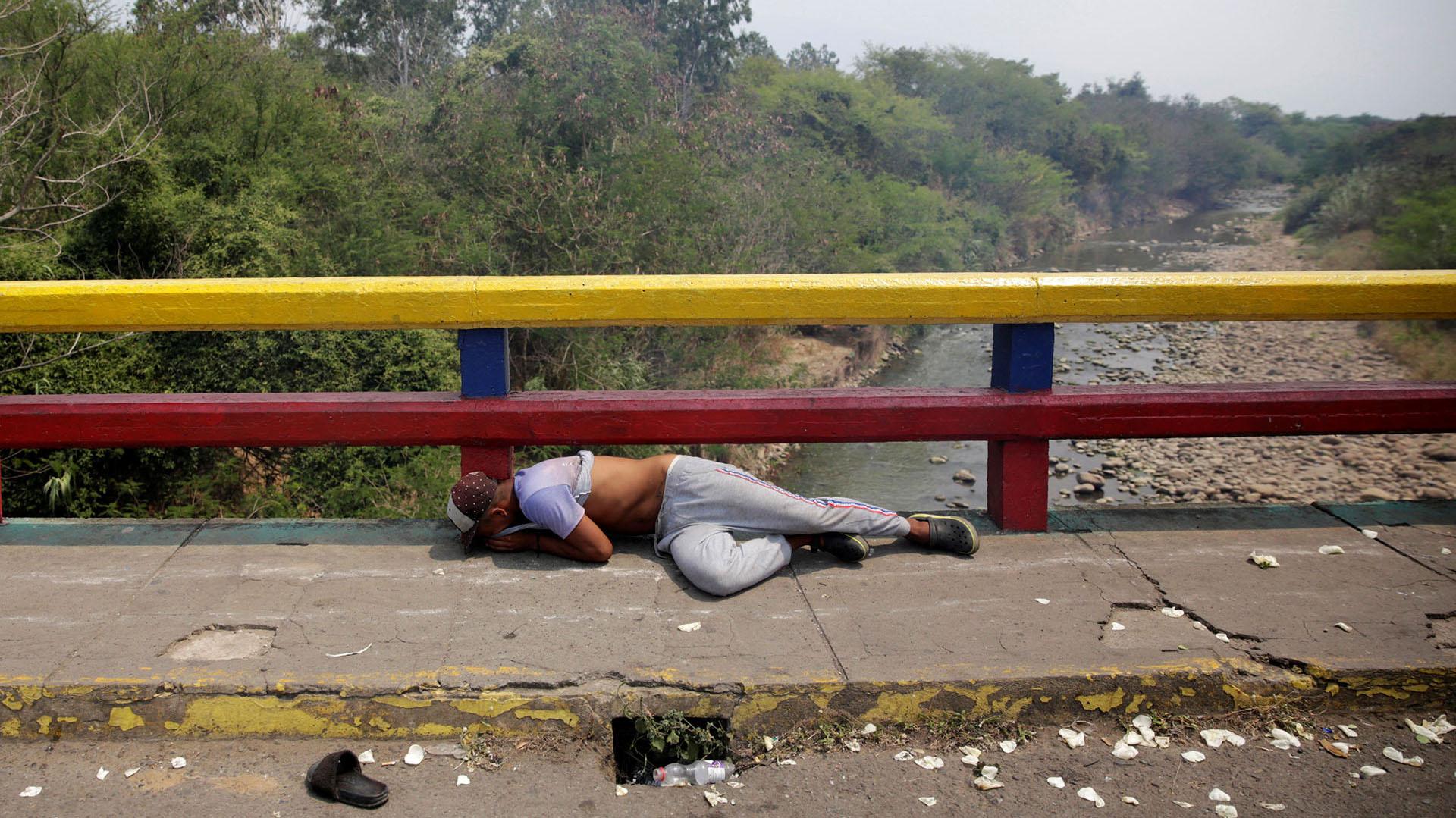 Un manifestante se encuentra en el suelo mientras se enfrenta a las fuerzas de seguridad de Venezuela en el puente Francisco de Paula Santander en la frontera entre Colombia y Venezuela, visto desde Cucuta (Reuters)