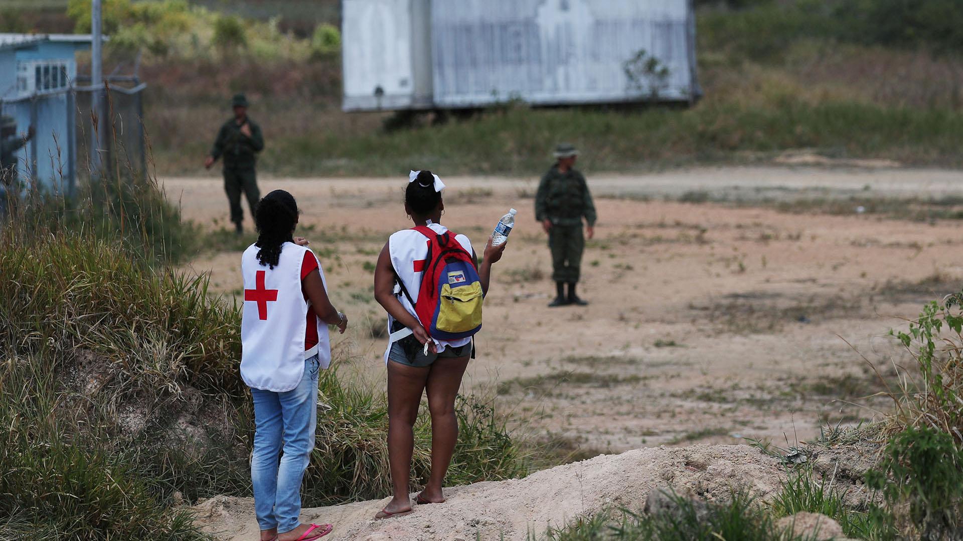Los voluntarios ofrecen agua a los soldados venezolanos en la frontera entre Venezuela y Brasil en Pacaraima, Brasil (Reuters)