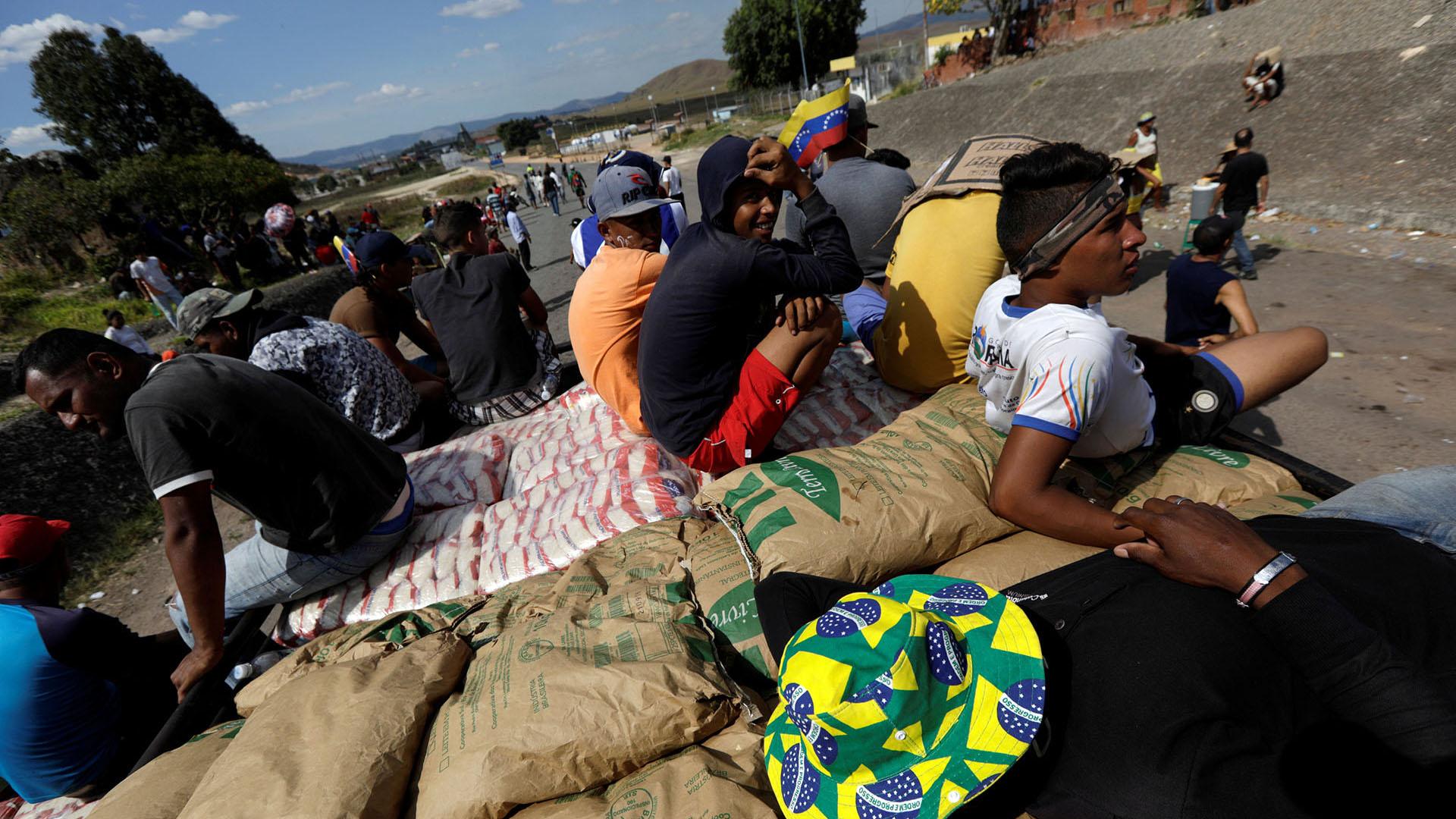 Los voluntarios descansan en un camión que lleva ayuda humanitaria mientras cruza a Venezuela desde Brasil (Reuters)