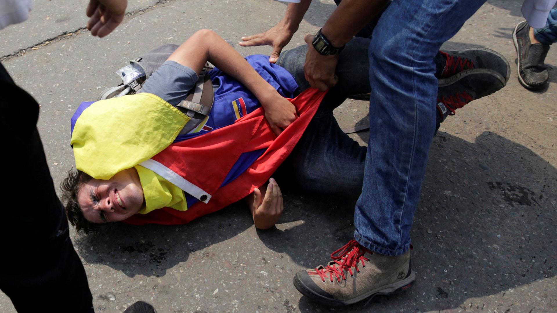 Un manifestante lesionado recibe ayuda de otros mientras se enfrenta a las fuerzas de seguridad de Venezuela en el puente Francisco de Paula Santander en la frontera entre Colombia y Venezuela (Reuters)