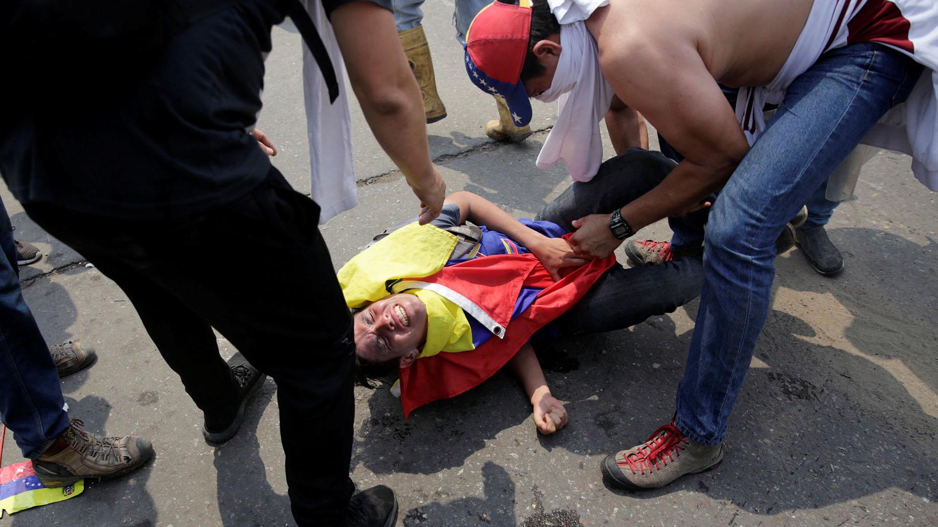 Un manifestante lesionado recibe ayuda de otros mientras se enfrenta a las fuerzas de seguridad de Venezuela en el puente Francisco de Paula Santander en la frontera entre Colombia y Venezuela, visto desde Cúcuta, Colombia (reuters)