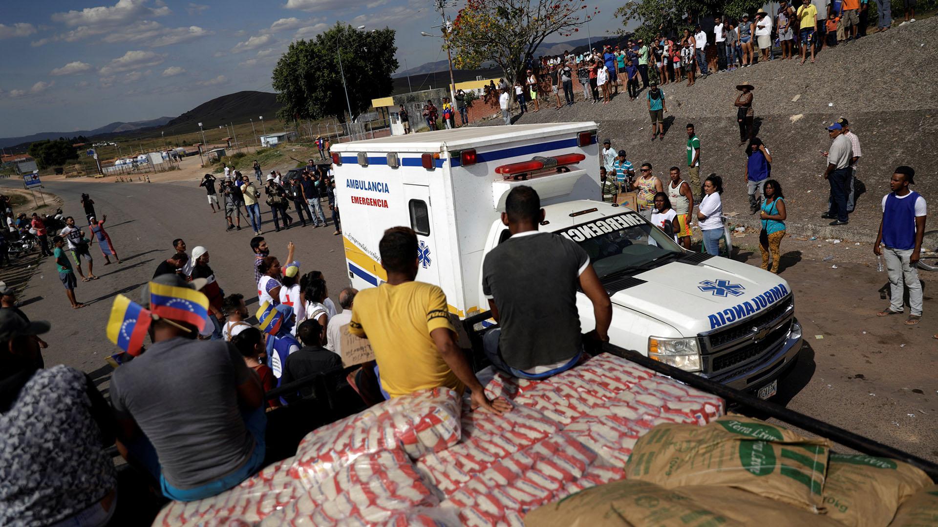 Una ambulancia que transporta personas heridas de Venezuela, pasa junto a un camión con ayuda humanitaria en la frontera entre Venezuela y Brasil en Pacaraima, Brasil (Reuters)