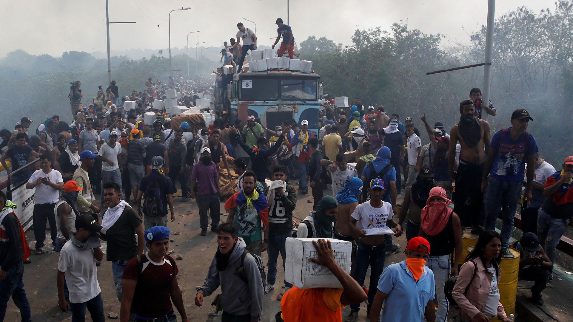 Opositores descargan alimentos de los camiones tras ser atacados por orden de Nicolás Maduro en uno de los pasos fronterizos (Reuters)