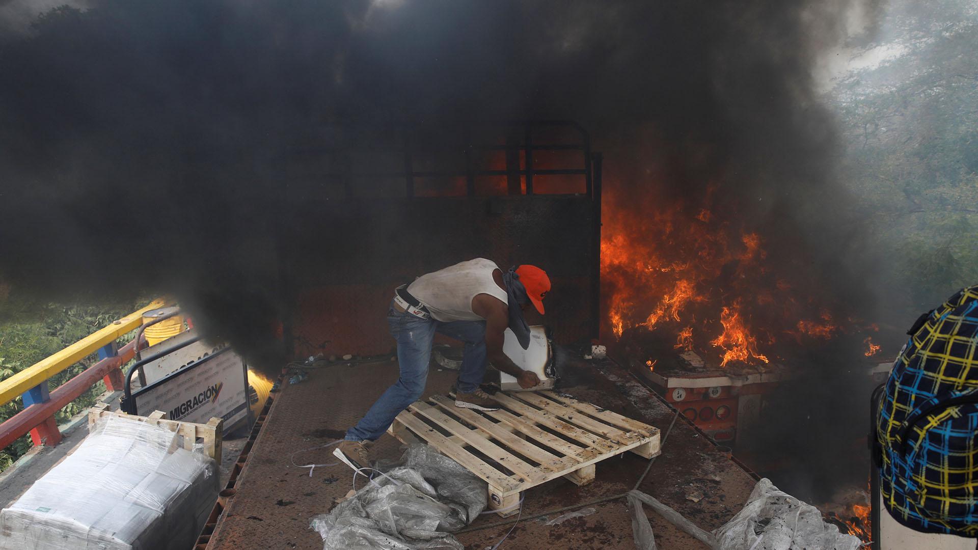 Partidarios de la oposición descargan ayuda humanitaria de un camión que fue incendiado luego de enfrentamientos entre simpatizantes de la oposición y las fuerzas de seguridad de Venezuela en el puente Francisco de Paula Santander en la frontera entre Colombia y Venezuela visto desde Cúcuta (Reuters)