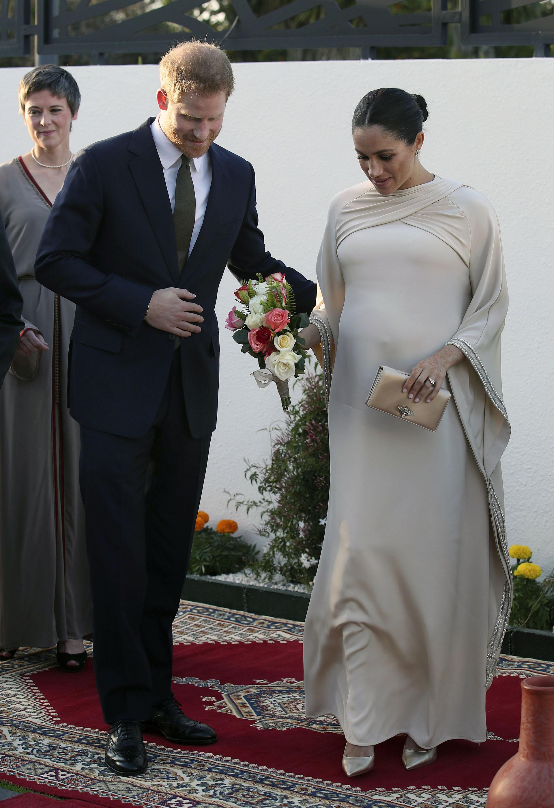 La duquesa de Sussexpresumió otro look glamoroso para una recepción en la alfombra roja organizada por el Embajador británico en Marruecos. Meghan llevaba un vestido con capa a medida de Dior, además de unsobre de oro a juego del mismo diseñador (AP)