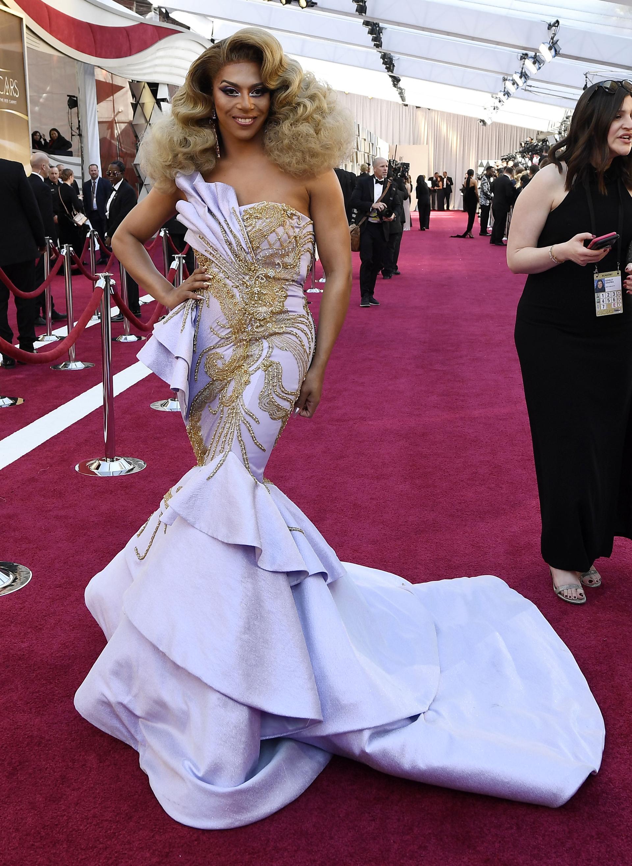 La drag queenShangelacon un vestido sirena en lila y detalles dorados. Un look extravagante pero con mucha personalidad