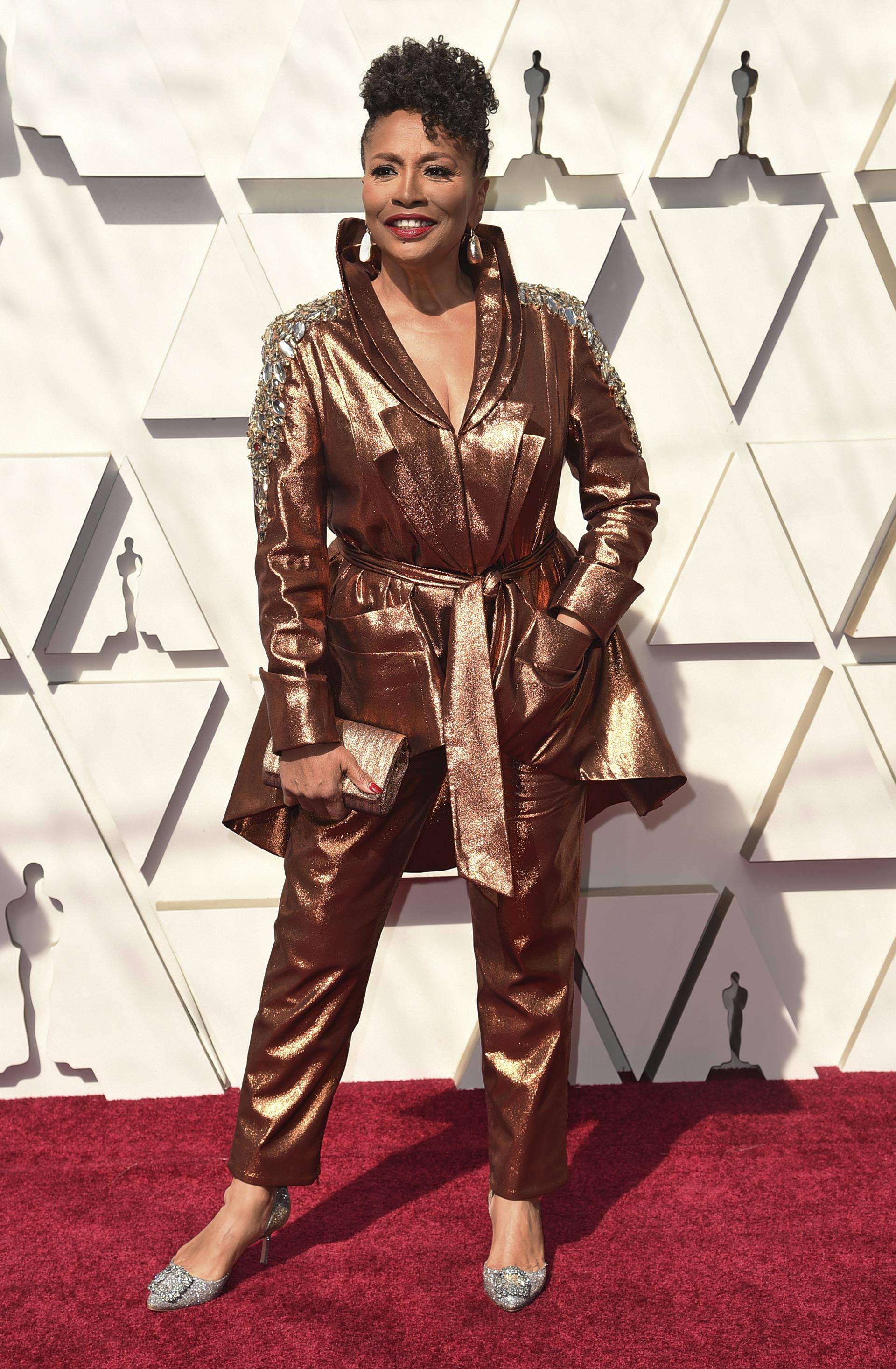 Jenifer Lewis apostó al metalizado. Un traje de dos piezas en bronce. Saco con hombreras bordadas de piedras y pantalón, completó el look con stilettos plateados de Manolo Blahnik y clutch rígido en bronce