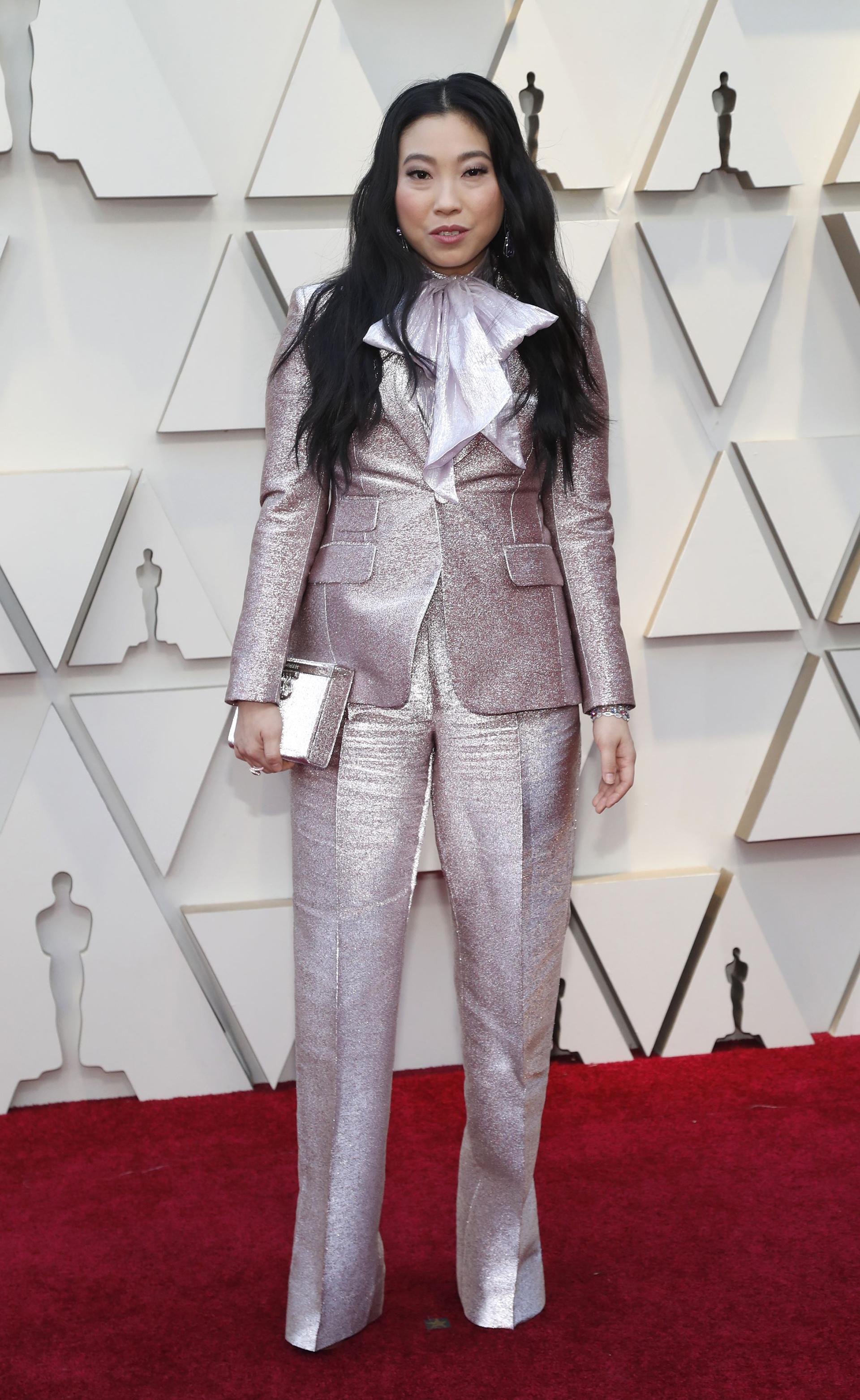 La actriz y cantanteAwkwafina con un traje metalizado de dos piezas con pantalón tiro alto, con foulard estilo moño y cartera rígida haciendo juego