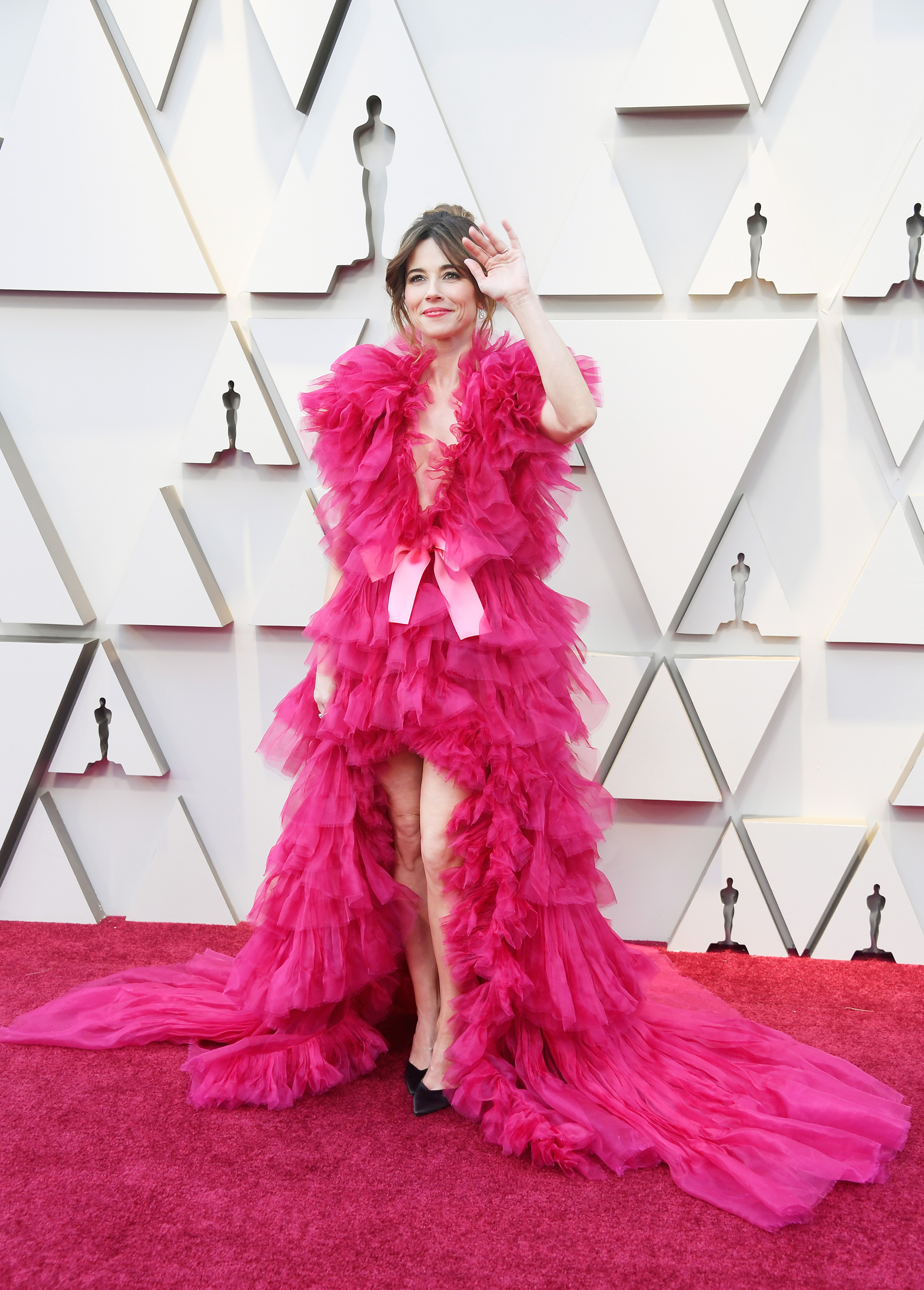 """La actrizLinda Cardellini, de """"Green Book"""", con un vestido realizado con tul fucsia en cascadas y un escote profundo"""