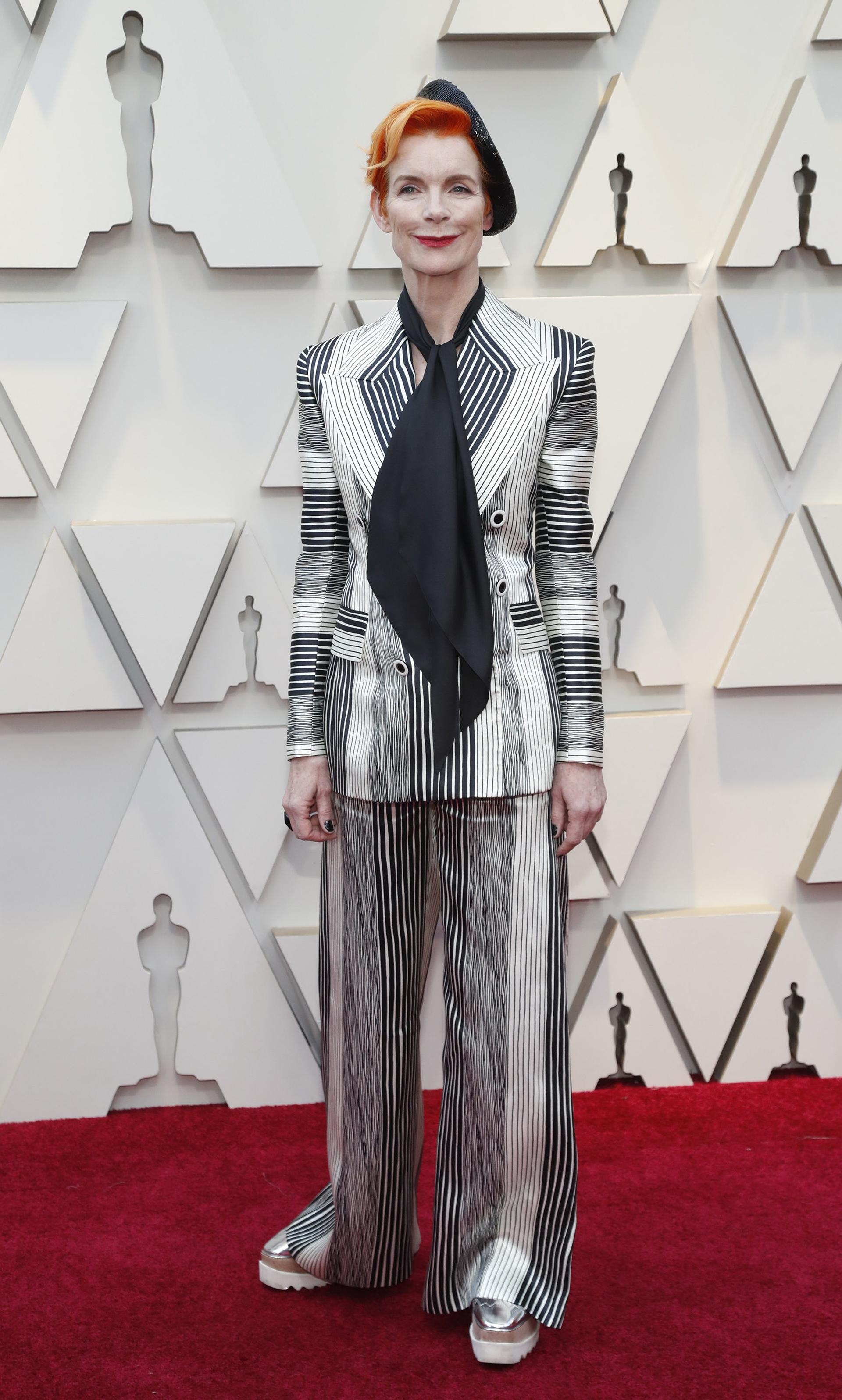 Sandy Powell impactó con un look masculino rayado en blanco, gris y negro. Completó el look con un foulard, los clásicos zapatos de Stella McCartney y boina negra