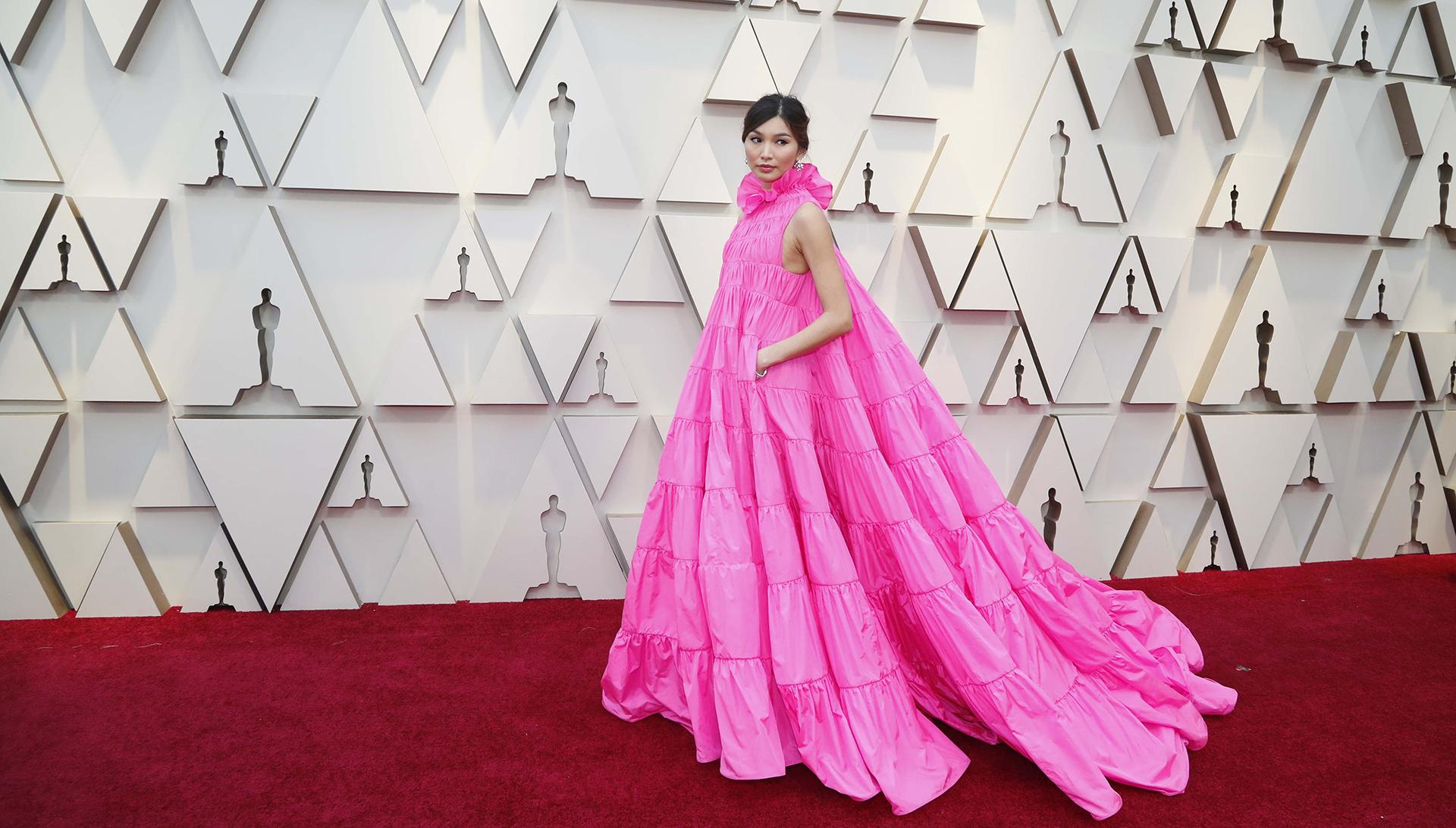 La actriz Gemma Chan sorprende en la alfombra roja con un vestido de Valentino línea A en color fucsia sin mangas y cuello con volados
