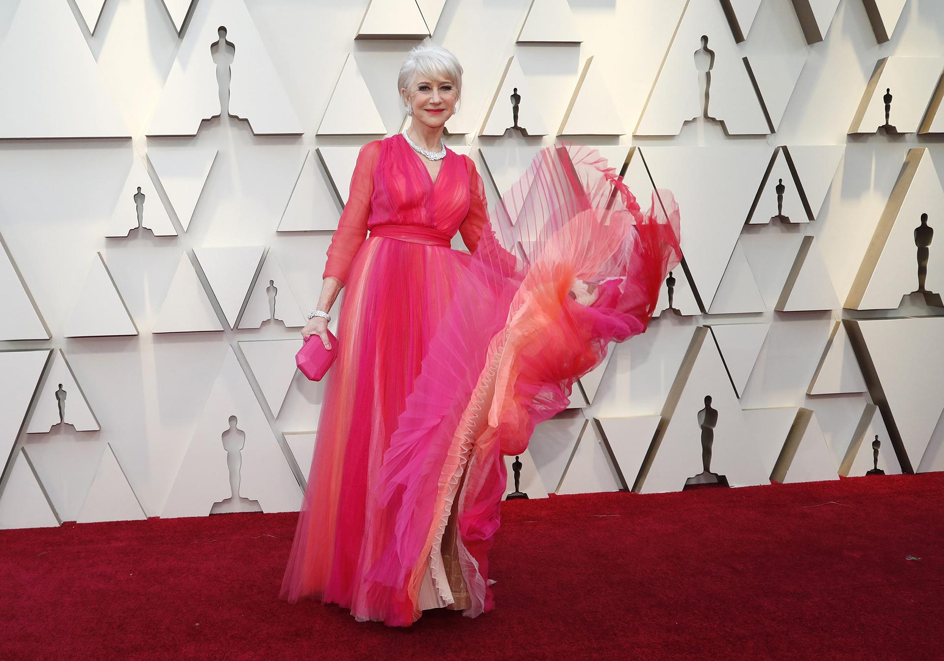 La actriz británica Helen Mirren lució un vestido fucsia con diferentes tonos y mucho tul, con mangas largas con transparencias y un clutch rígido