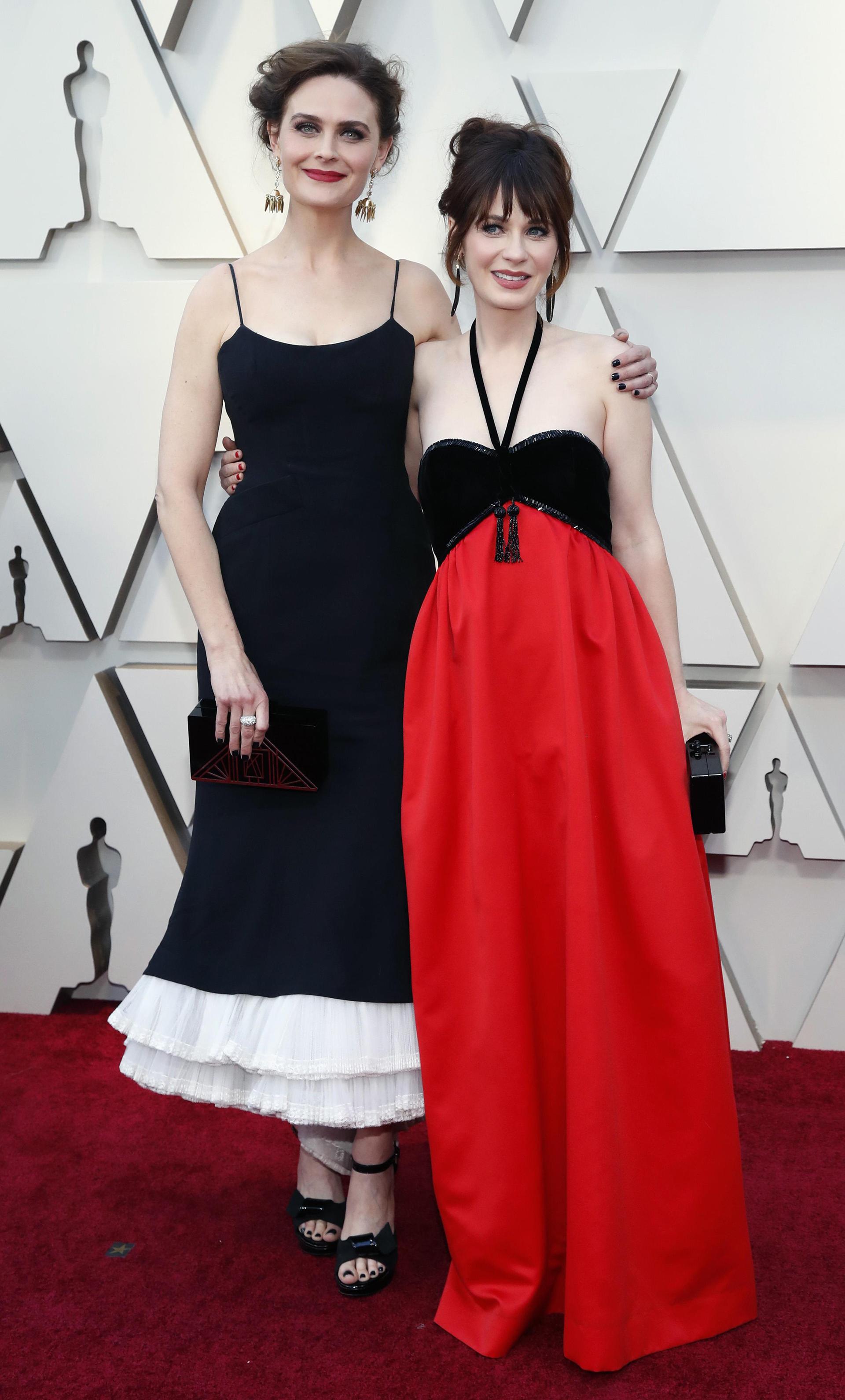 Zooey y Emily Deschanel. Las actrices dieron presente en la red carpet con estilos diferentes. Zooey con un vestido al tobillo con corte en la cintura y detalle de plisado blanco con sandalias y clutch rígido.