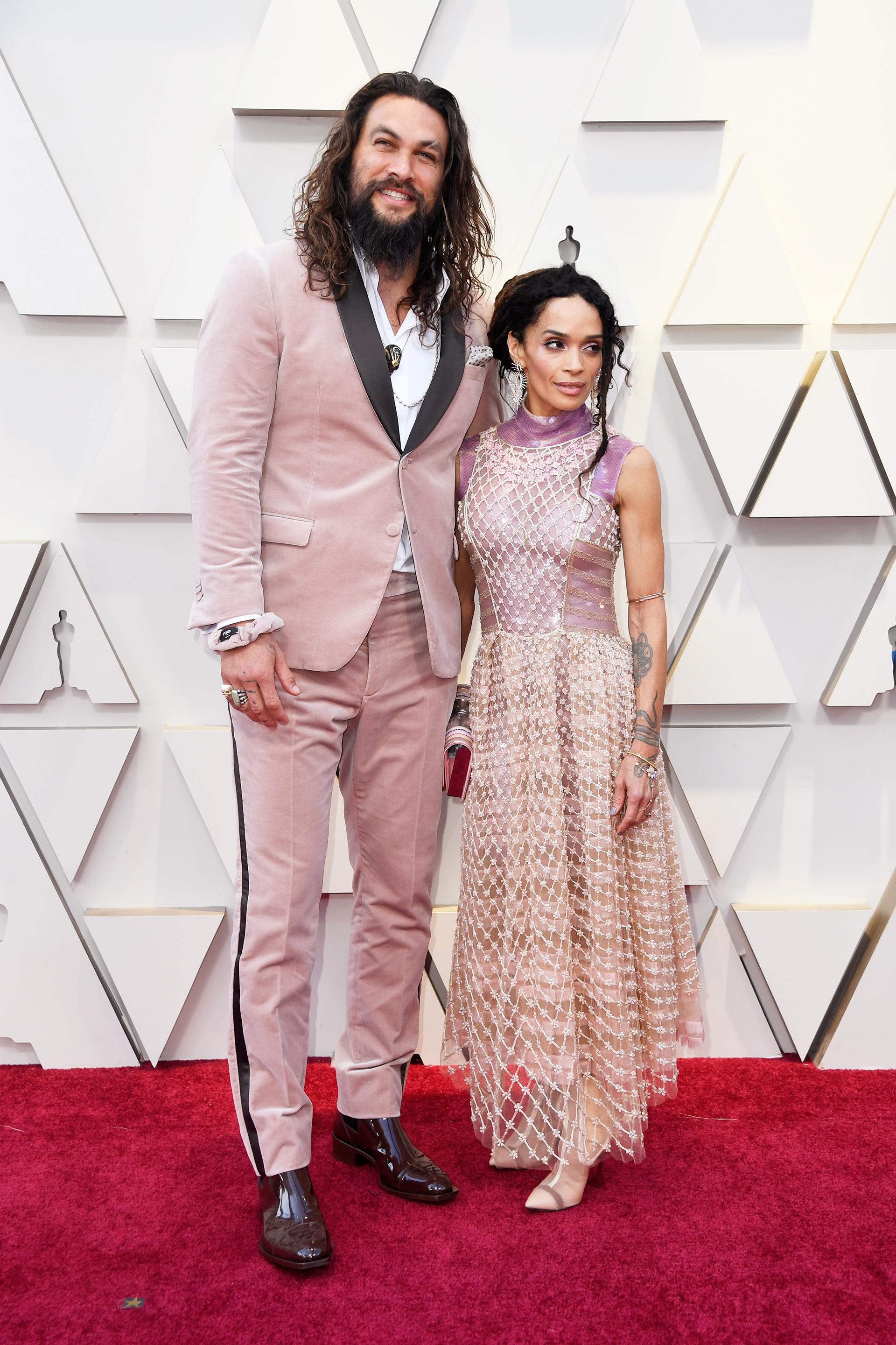 Jason Momoay Lisa Bonet son una de las parejas más sexy de Hollywood, pero esta vez no acertaron. Ambos a juego, él optó por un traje de terciopelo rosa viejo con envivados en negro, y ella por un vestido nude con red y envivados en terciopelo lila.