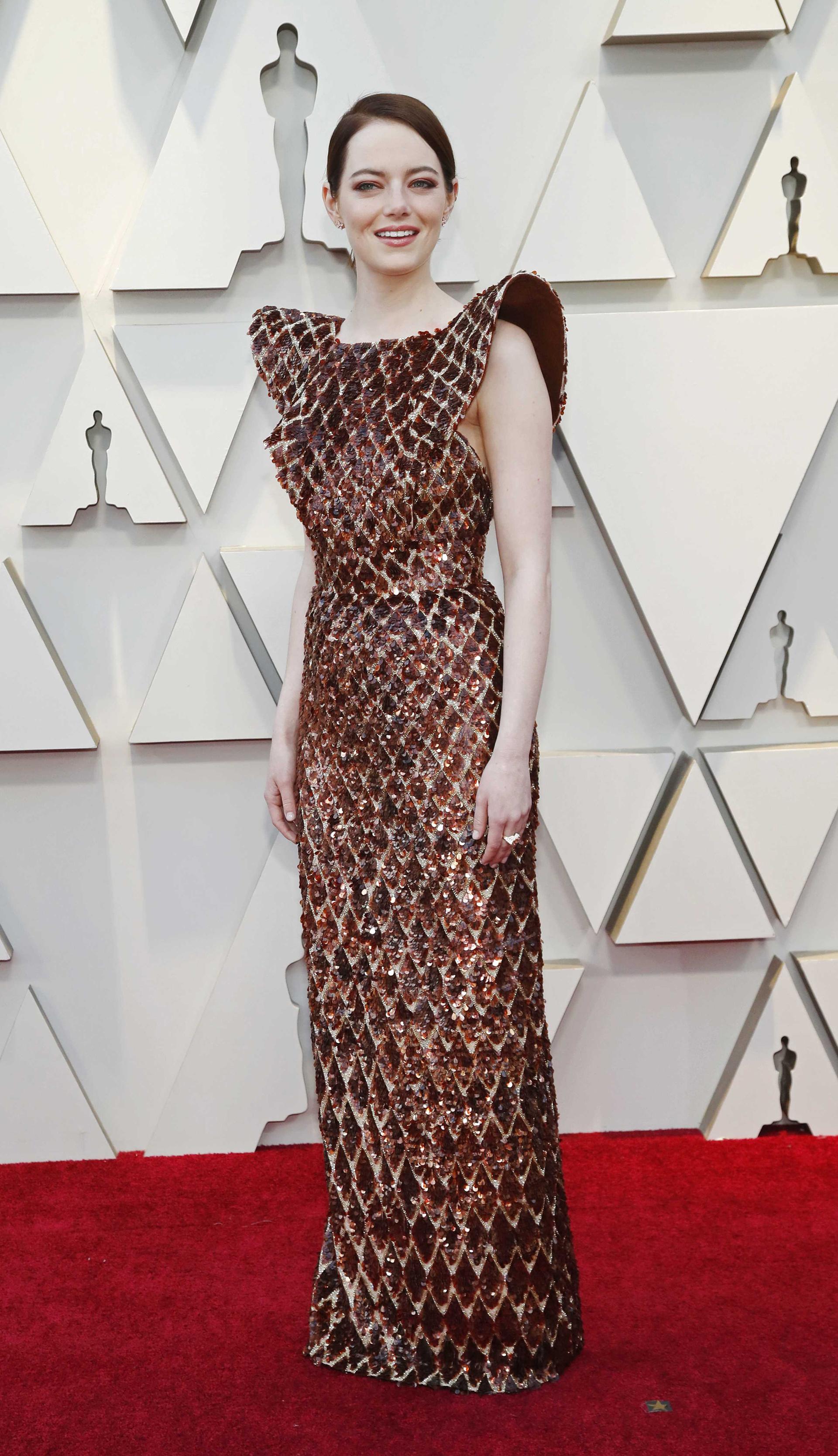 Emma Stone sorprendió con su vestido de paillettes en bronce de rombos y hombros armados. Completó el look con un anillo y pequeños aros. Su beauty look, smokey eye en marrones y labios nude