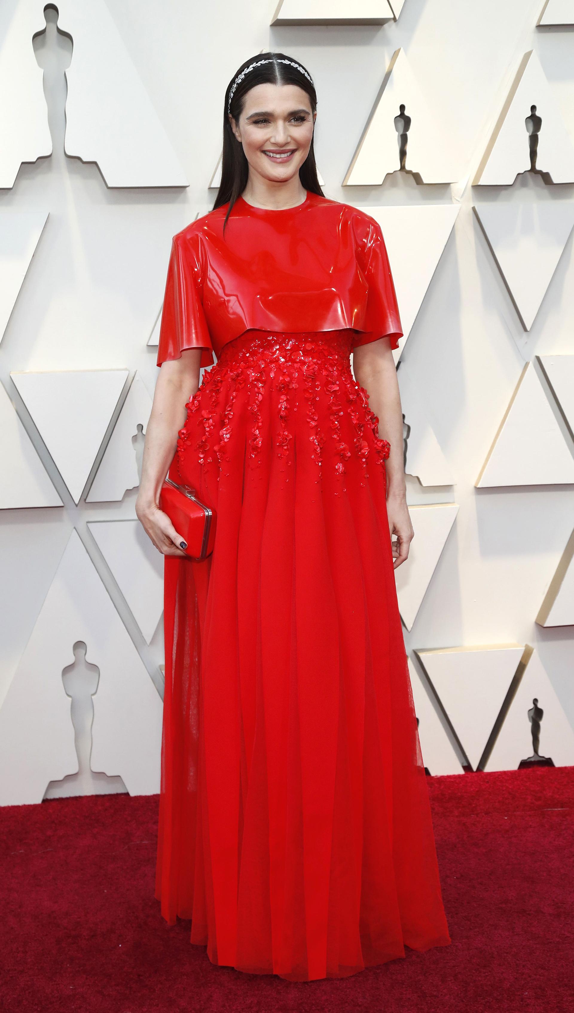 Rachel Weisz apostó al total red look. Con superposición de prendas, un top de vinilo y vestido plisado bordado, completó el look con clutch rígido y vincha de laureles plateados