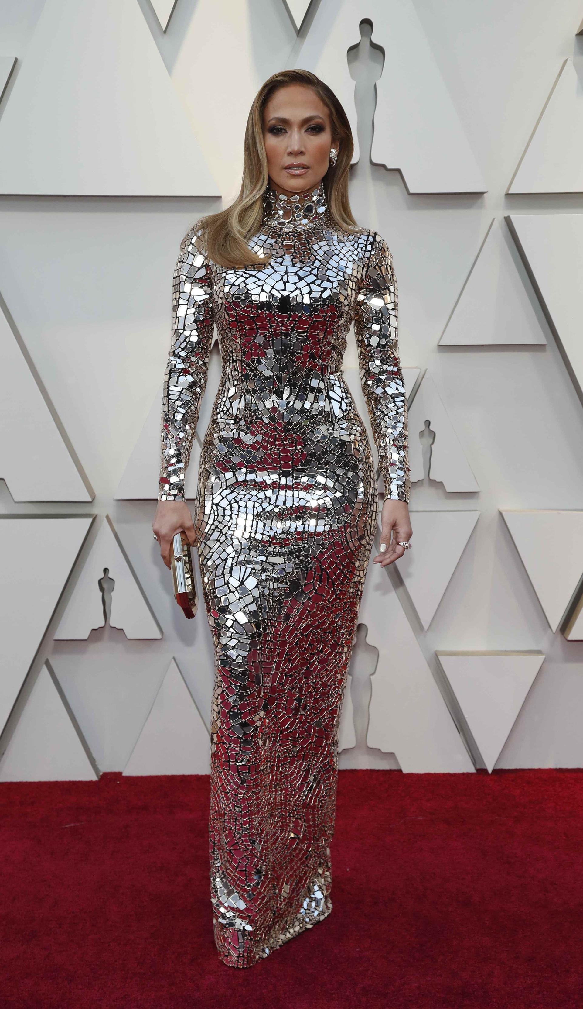 Jennifer Lopez enfundada en un vestido sirena con mangas largas y cuello polera de piedras plateadas. Completó el look con clutch rígido a tono y aros clip. Su beauty look, cabello lacio hacia un costado, smokey eyes y labios nude