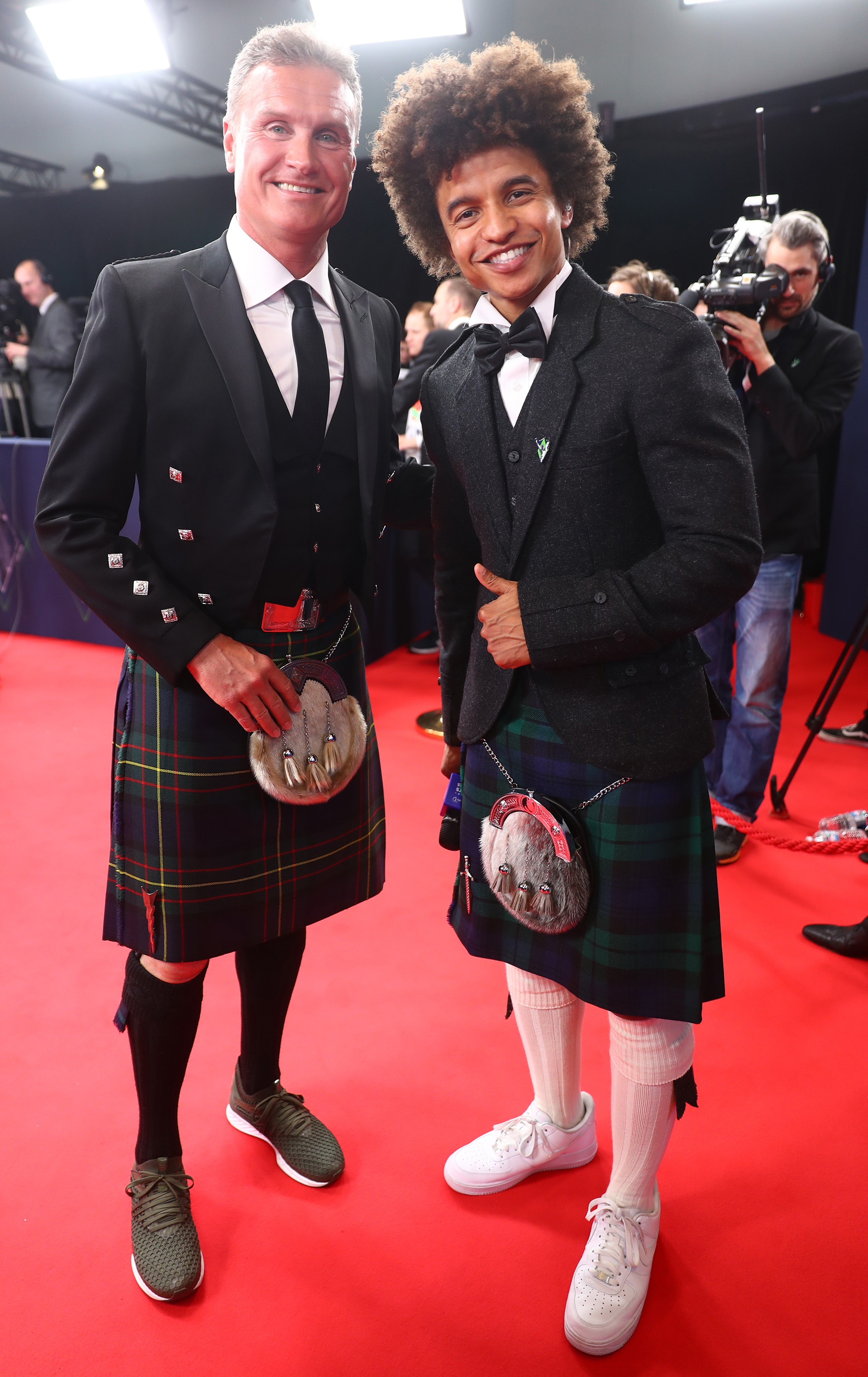 David Coulthardy Radzi Chinyanganya con look típicos escoceses