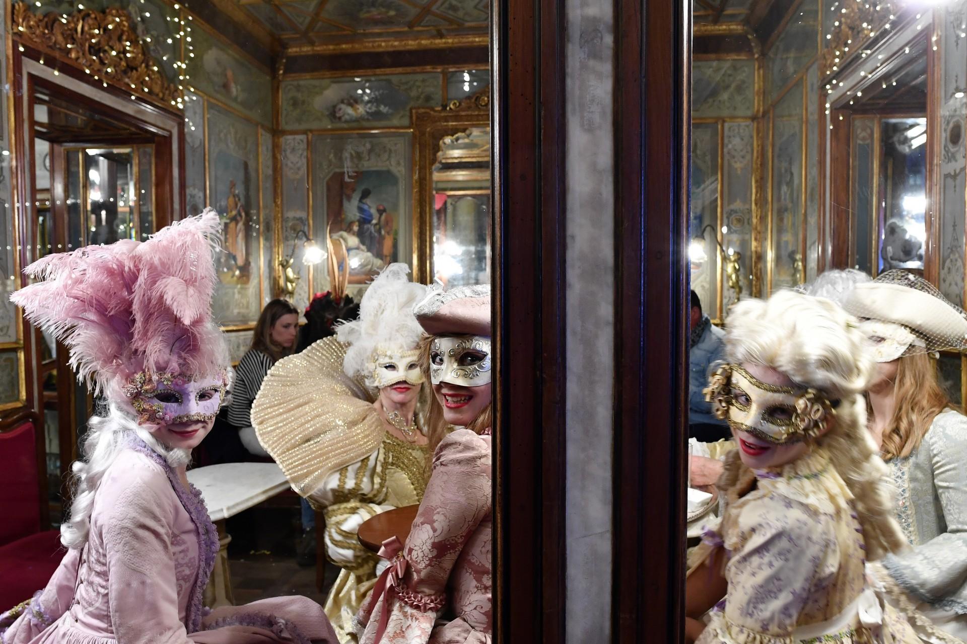 Unas chicas con máscaras y trajes de época se sientan en el café Florian durante el Carnaval de Venecia el 23 de febrero de 2019 en Venecia.