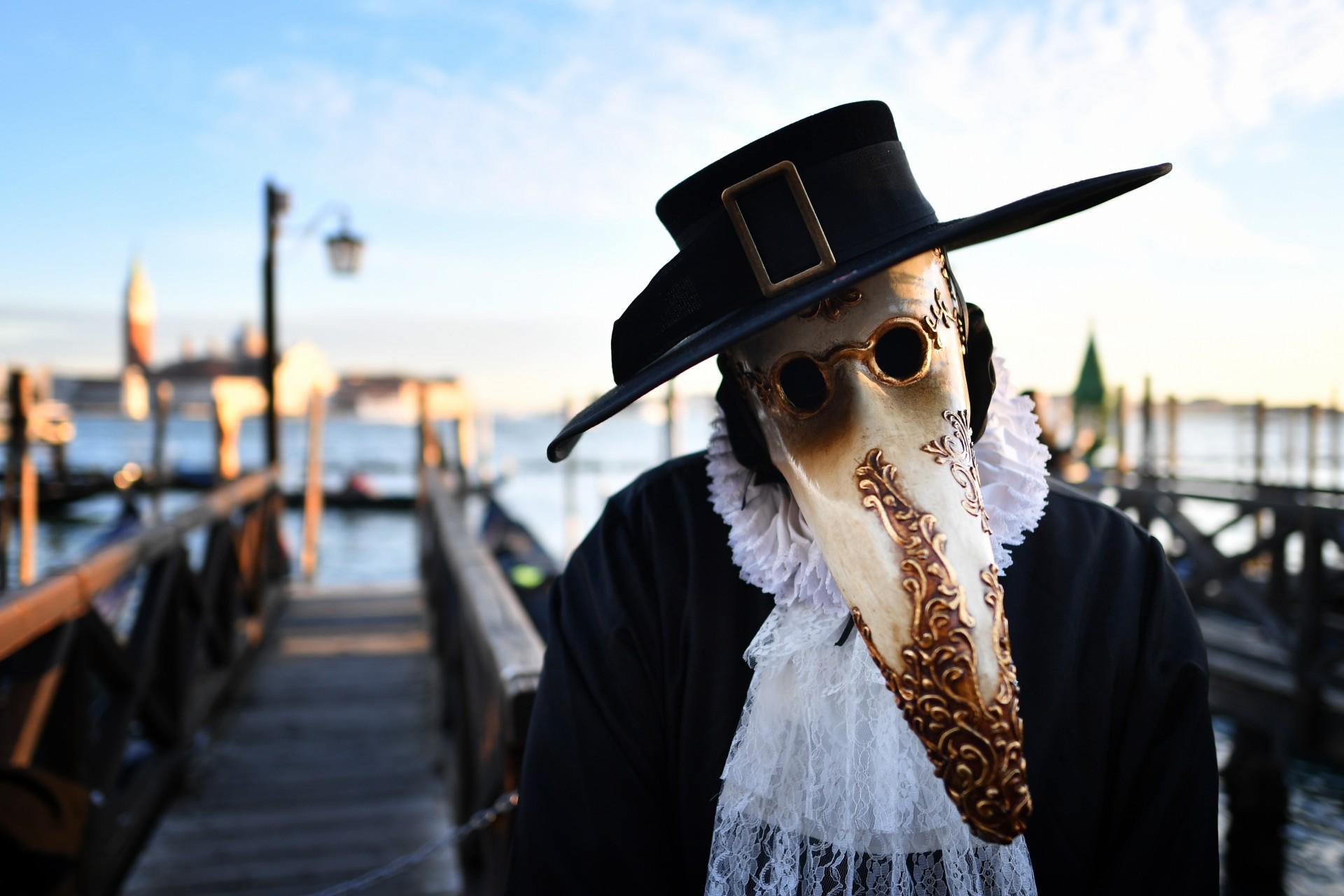 Un juerguista que lleva una máscara y un traje de época huele una rosa cuando participa en el Carnaval de Venecia el 24 de febrero de 2019 en Venecia.