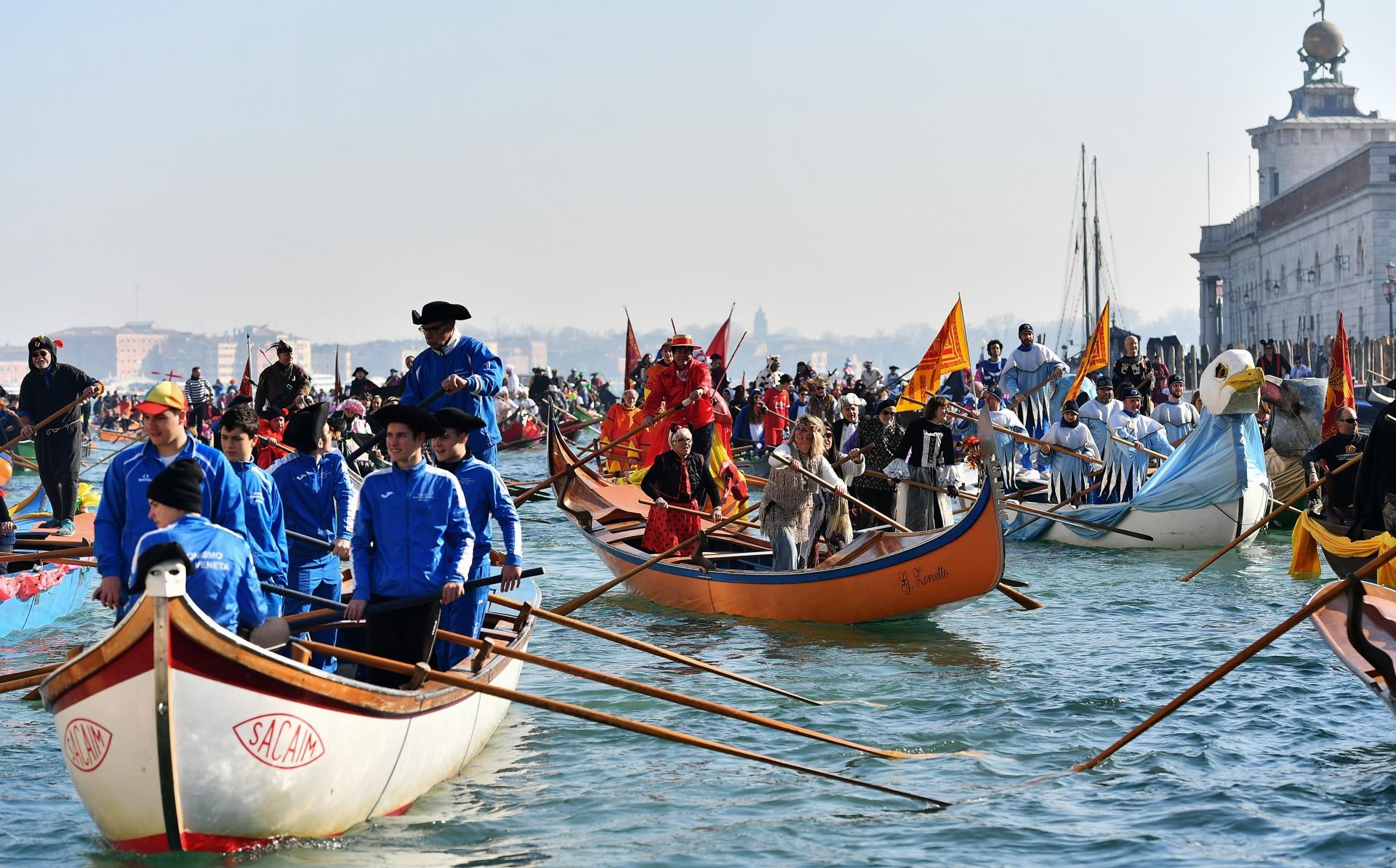 Los barcos decorados con juerguistas se mueven en el Gran Canal durante la regata de apertura del Carnaval de Venecia el 17 de febrero de 2019.