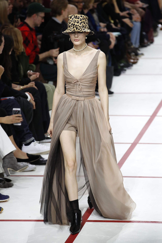 En pasarela un vestido-short de tul y seda drapeado con sobrefalda sin mangas. Como complemento, un collar de perlas y sombrero de animal print