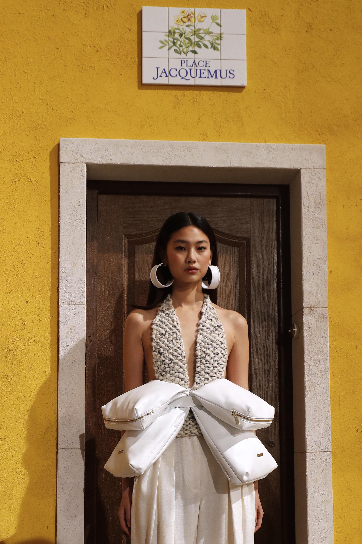 Un extravagante diseño de Jacquemus. Una maxi riñonera con 4 compartimientos. Un body tejido y un pantalón tiro medio de lino