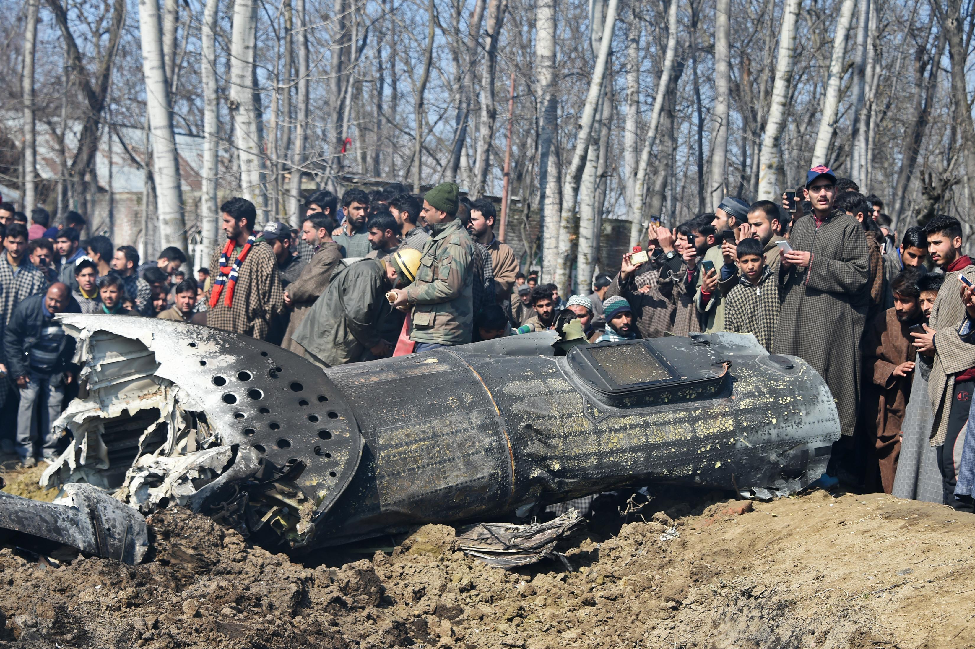 Soldados indios observan una aeronave india derribada por Pakistán en Cachemira (Photo by Tauseef MUSTAFA / AFP)