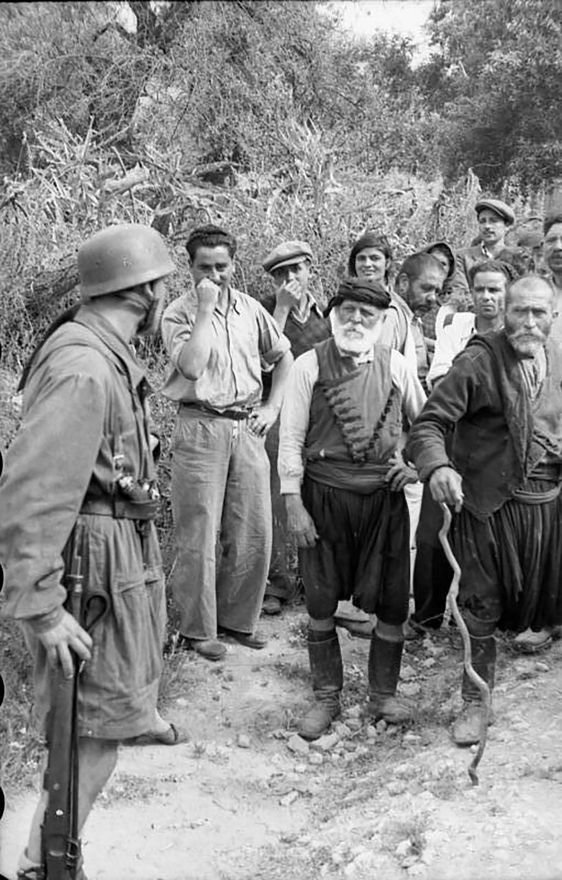 Civiles griegos cretenses se enfrentan a paracaidistas alemanes de Fallschirmjäger antes de que comenzara la masacre en Kondomari, Creta, en septiembre de 1941.