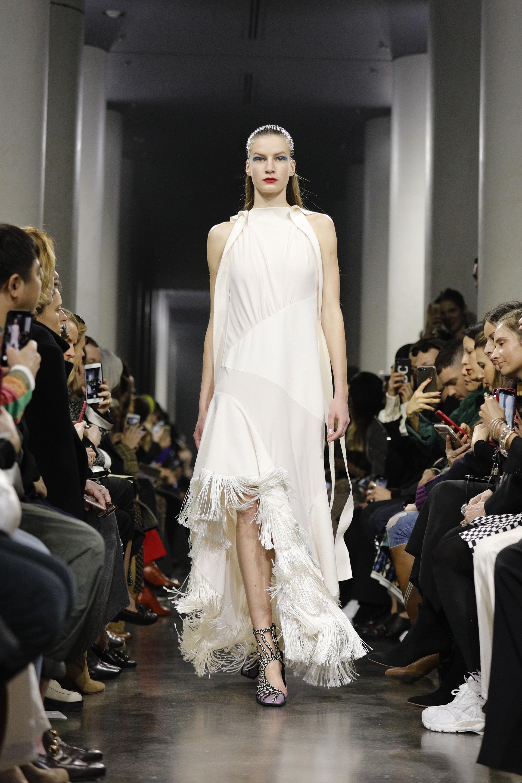 Off white, cuello halter, sin mangas, con flecos y tajo irregular. Con sandalias de animal print de cebra y lilas hasta el tobillo
