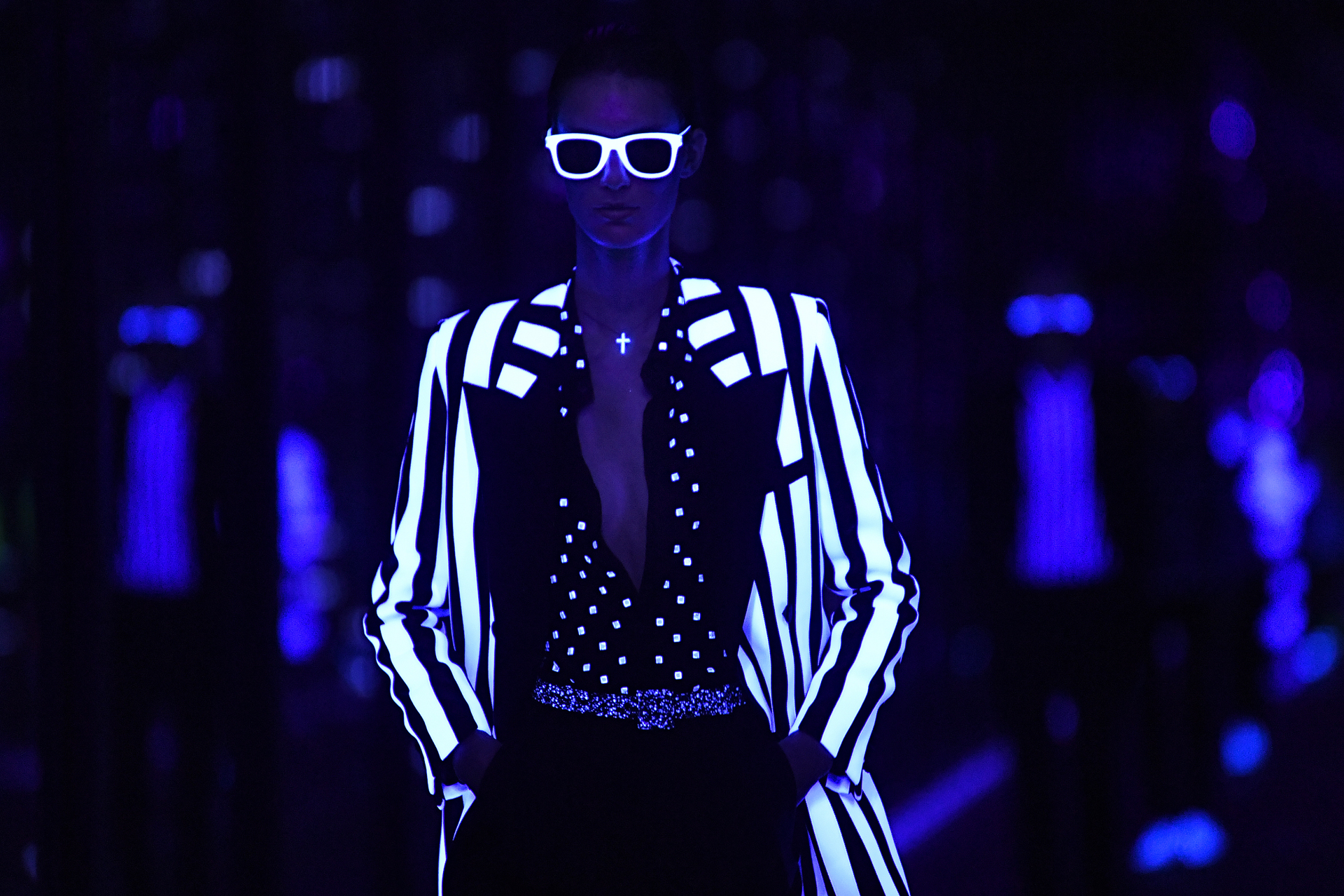 El efecto neón también llegó al esmoquin. Un saco rayado en blanco y negro, con blusa de polka dots, cinturón de glitter y pantalón negro