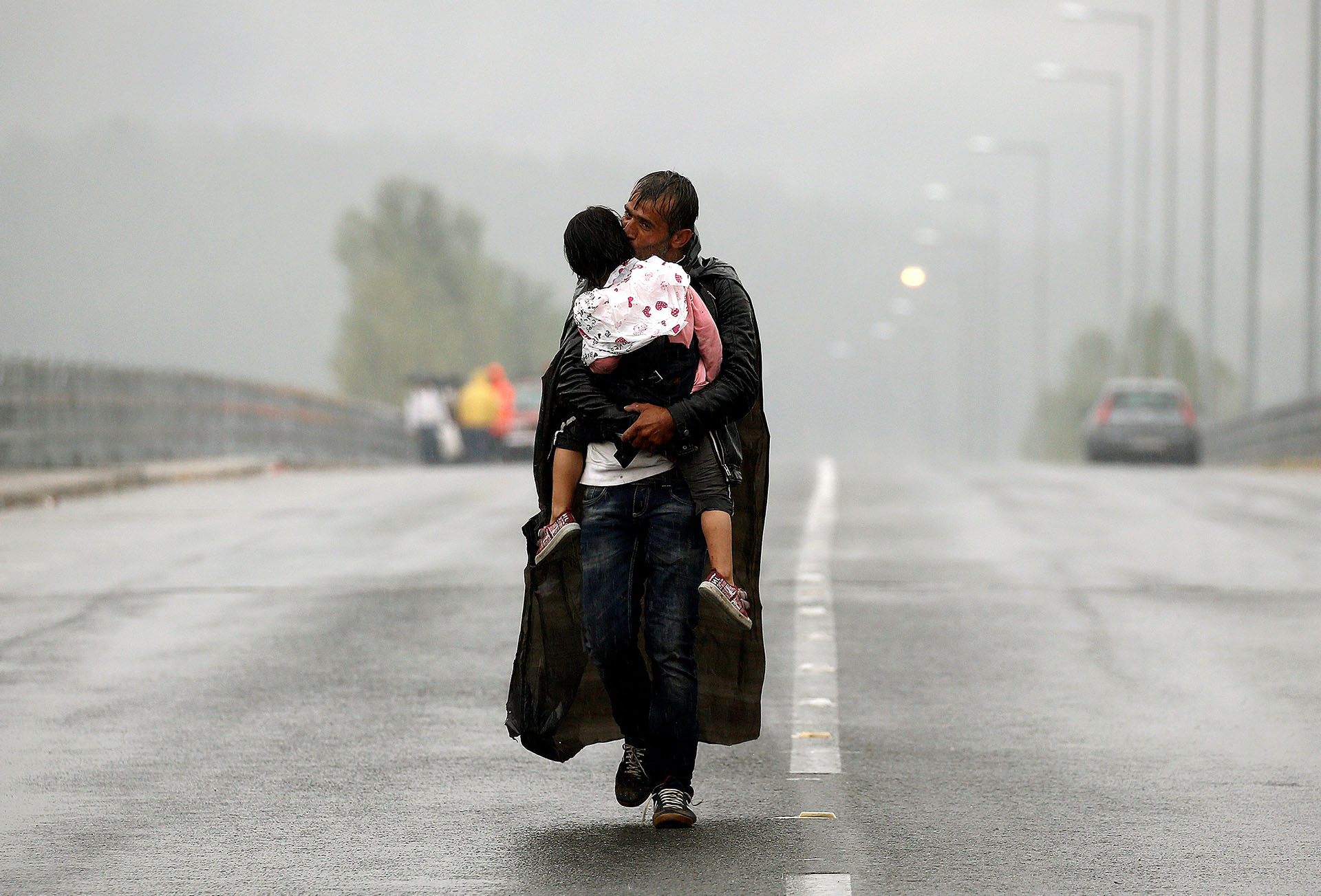 Un refugiado sirio besa a su hija mientras camina bajo la lluvia hacia la frontera entre Grecia y Macedonia, en septiembre de 2015