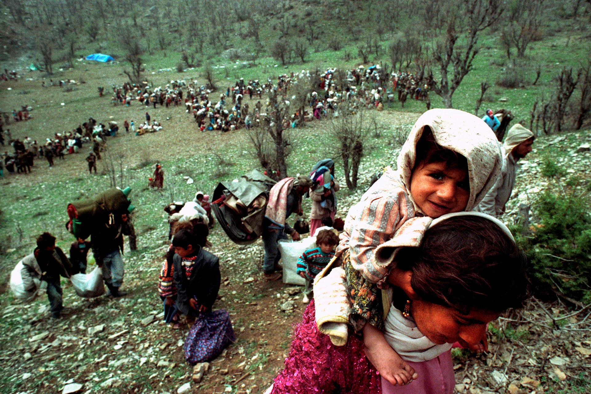 La sonrisa de una niña mientras refugiados kurdos escapan en la frontera entre Irak y Turquía, en abril de 1992