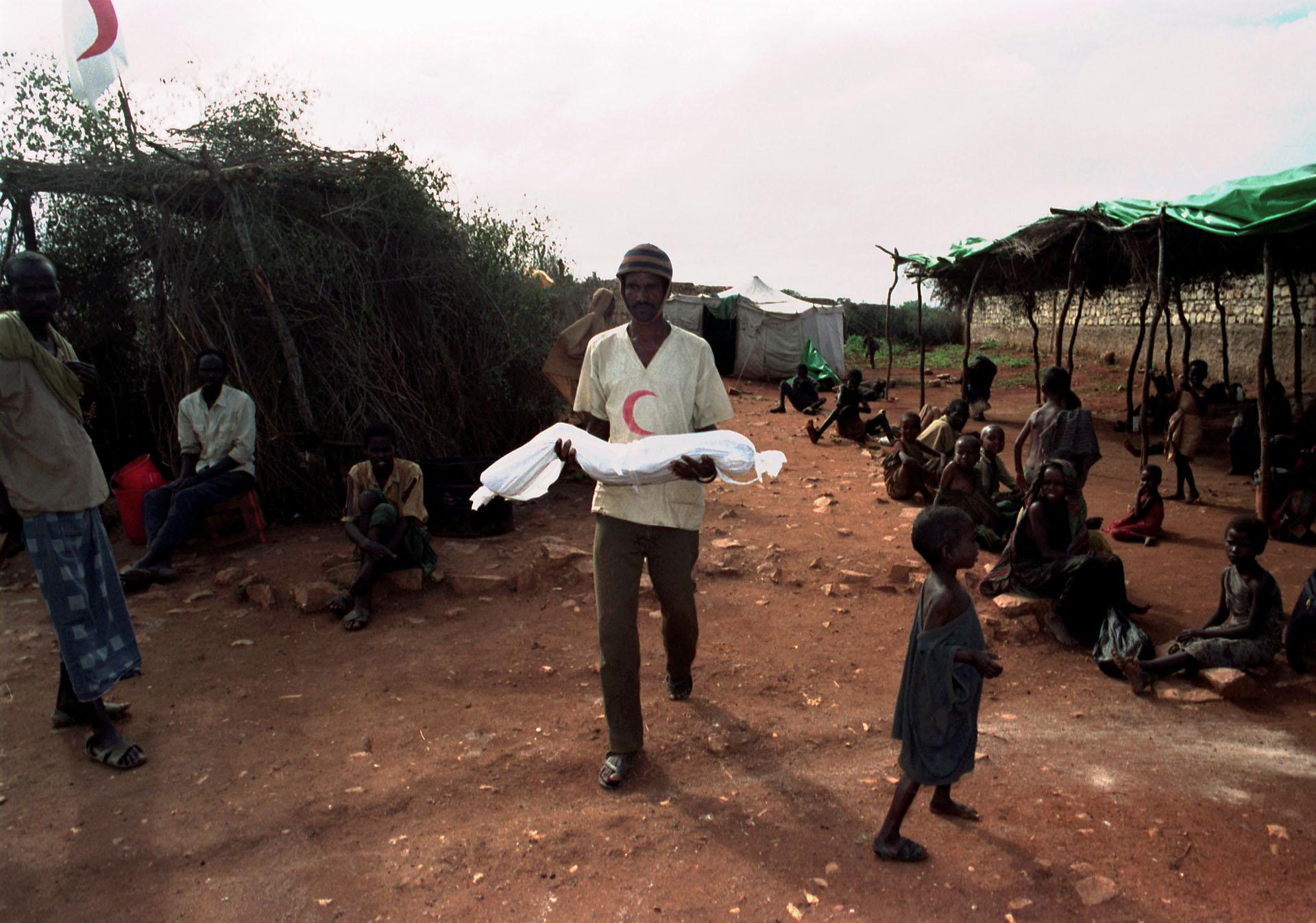 Un voluntario en Somalia carga el cuerpo de un menor en un campo de refugiados, en diciembre de 1992