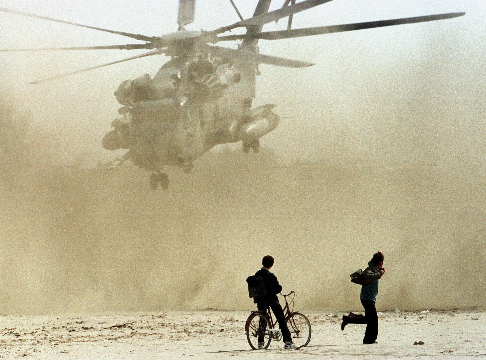 Dos albanos observan el despegue de un helicóptero estadounidense cerca al puerto de Durres. Las naves rescataban a ciudadanos norteamericanos del caos desatado en la zona
