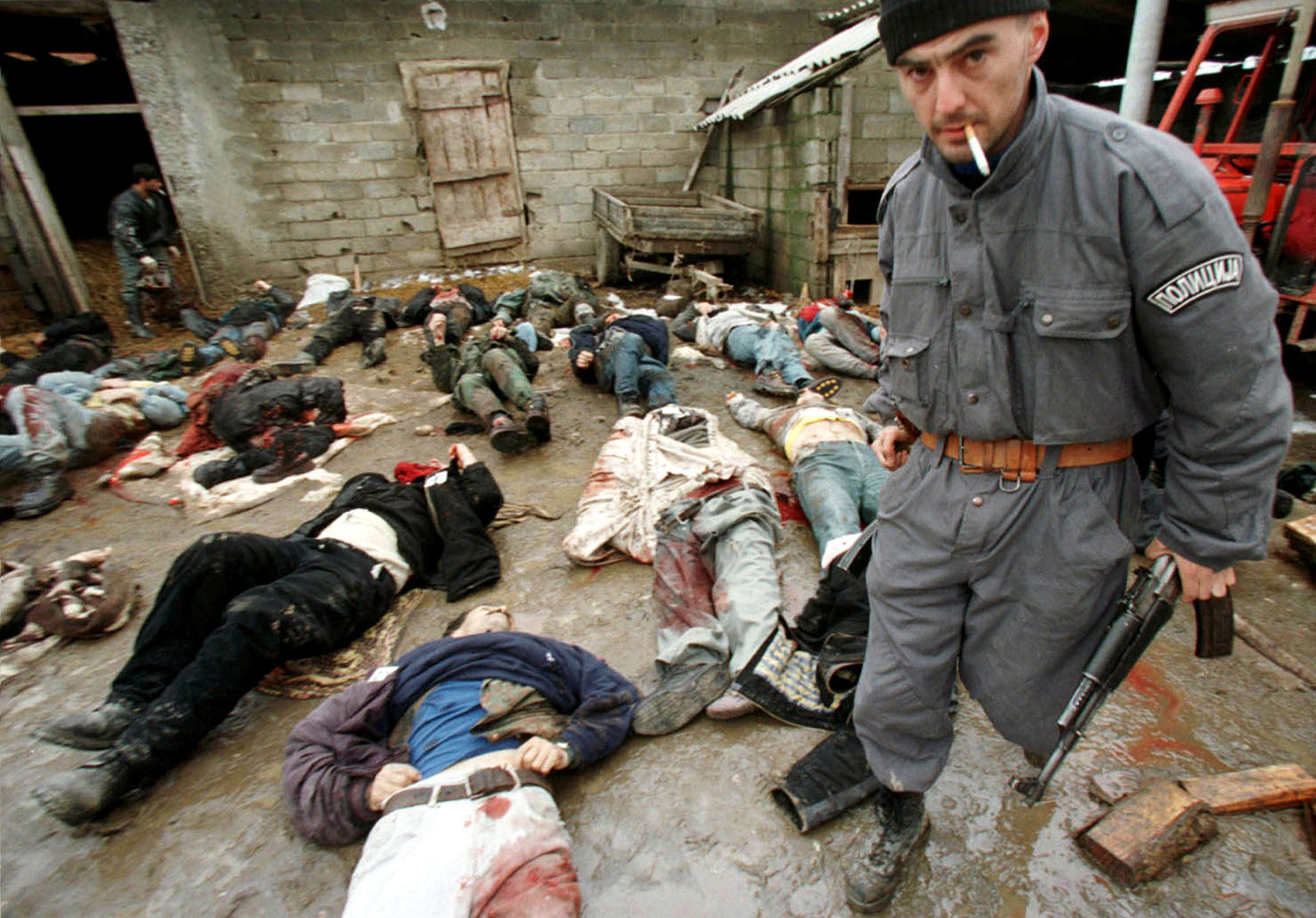 Un policía serbio recoge un rifle AK-47 de un guerrillero de Kosovo, en enero de 1999