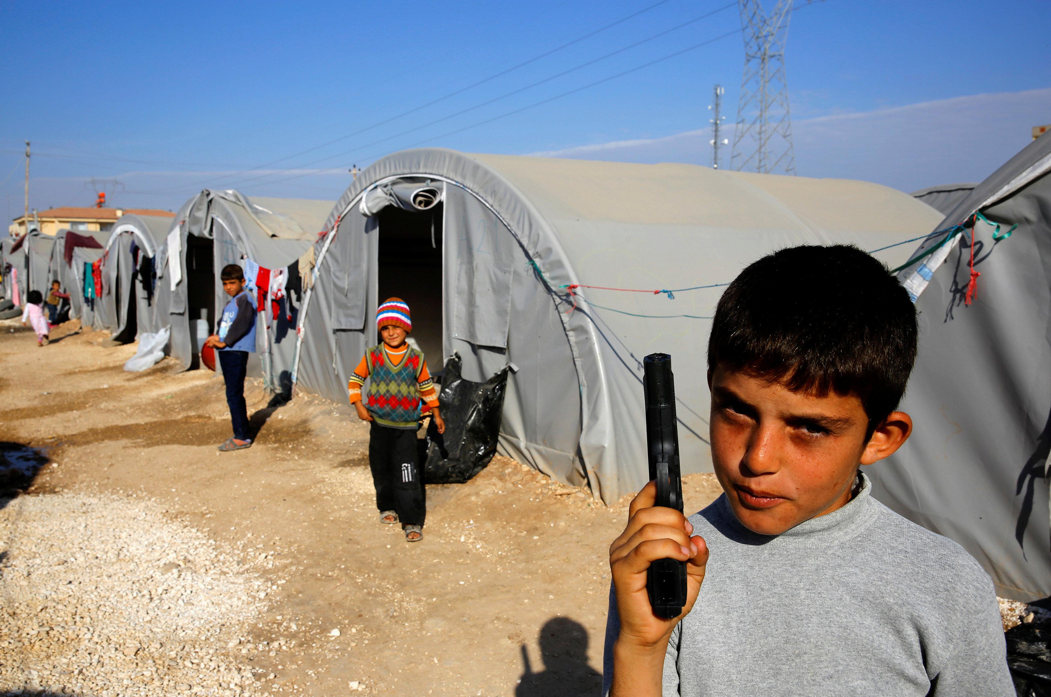 Un joven kurdo sostiene una pistola en un campo de refugiados, en octubre de 2014