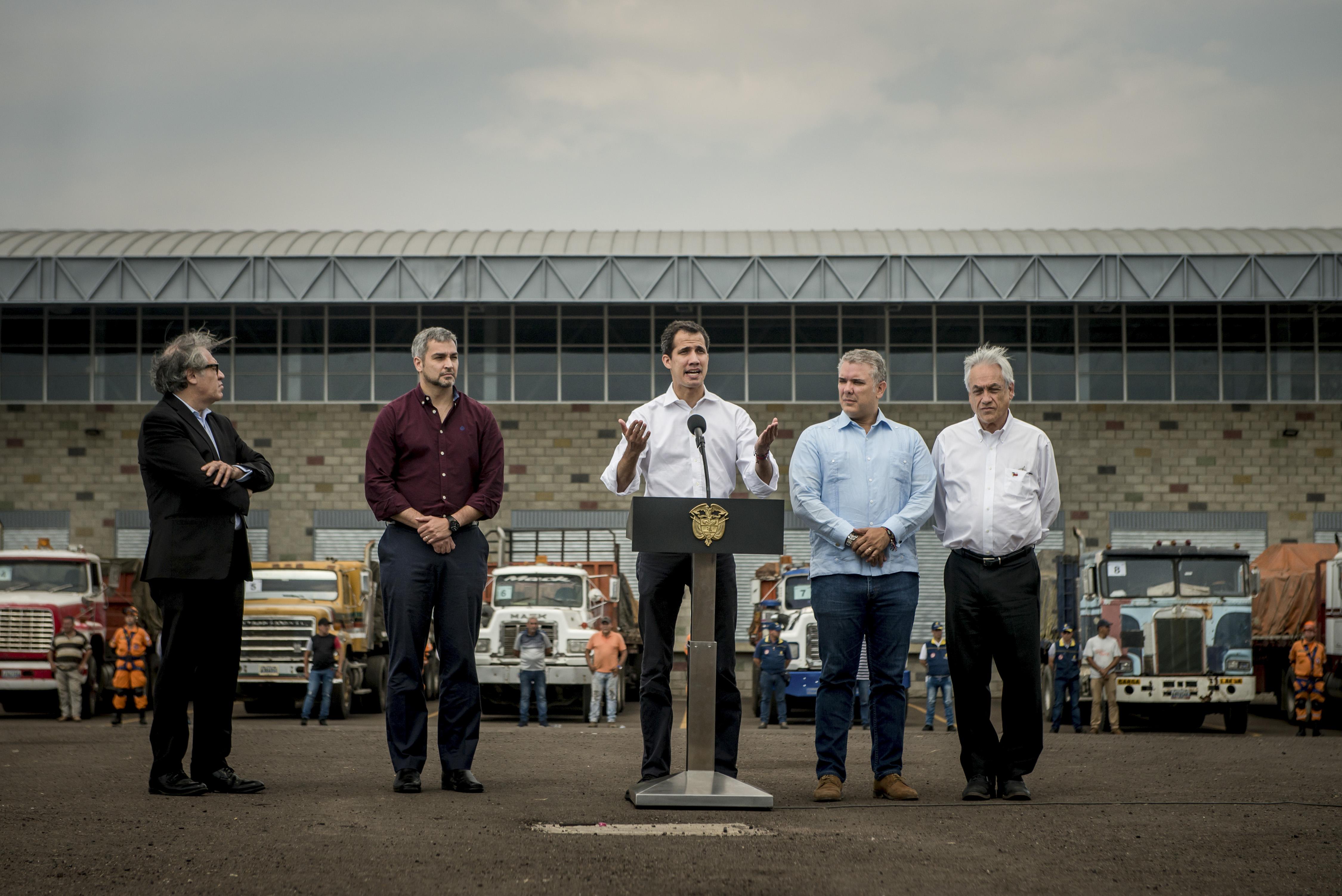 Guaidó, al centro, con los presidentes Sebastián Piñera de Chile, primero desde la derecha, e Iván Duque de Colombia, segundo desde la derecha, así como con Luis Almagro, secretario general de la Organización de Estados Americanos, OEA, primero desde la izquierda, frente a camiones con ayuda humanitaria en Colombia el 23 de febrero. (Meridith Kohut/The New York Times)