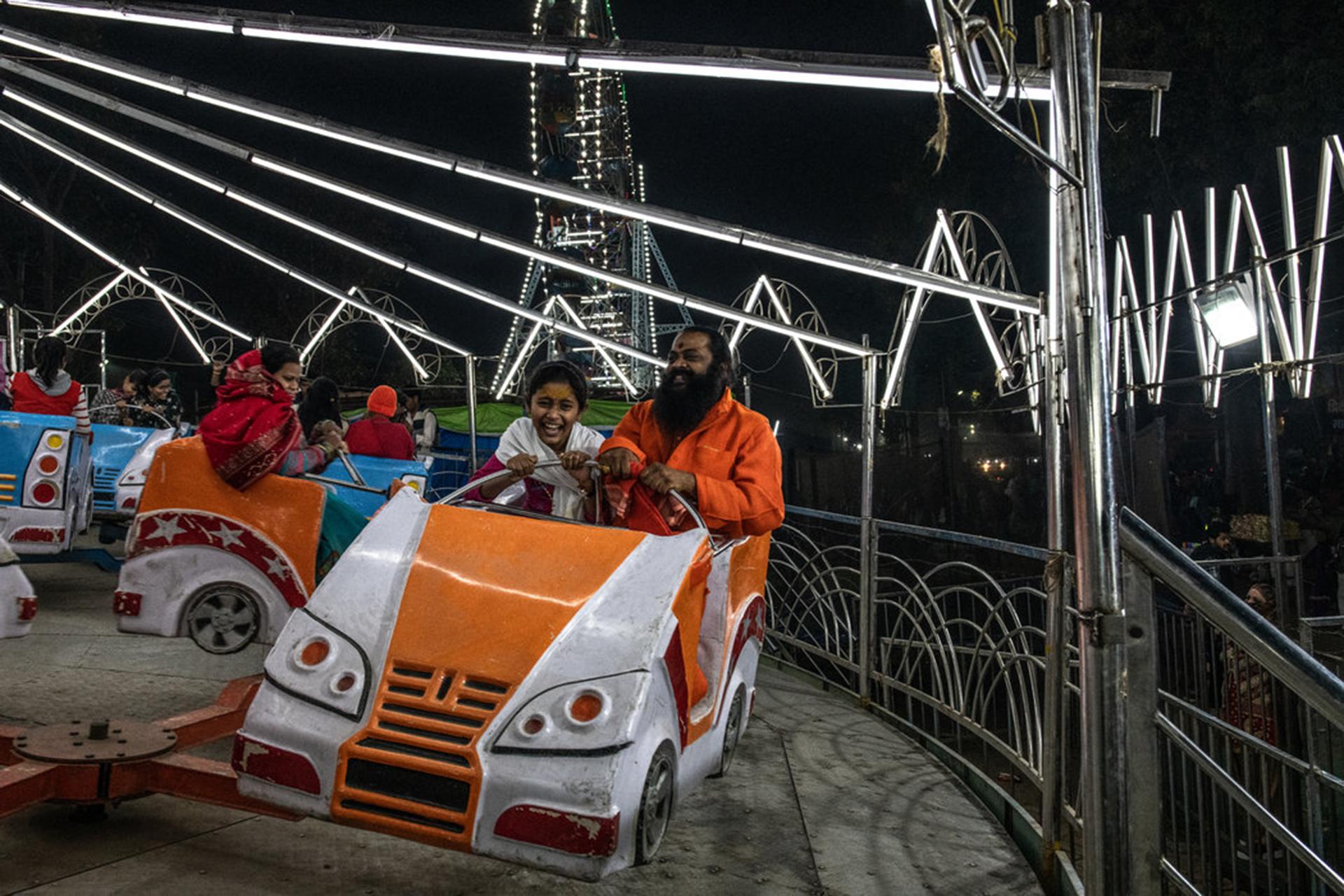 Un hombre santo y una niña disfrutaban de una de las atracciones mecánicas del festival. (The New York Times)