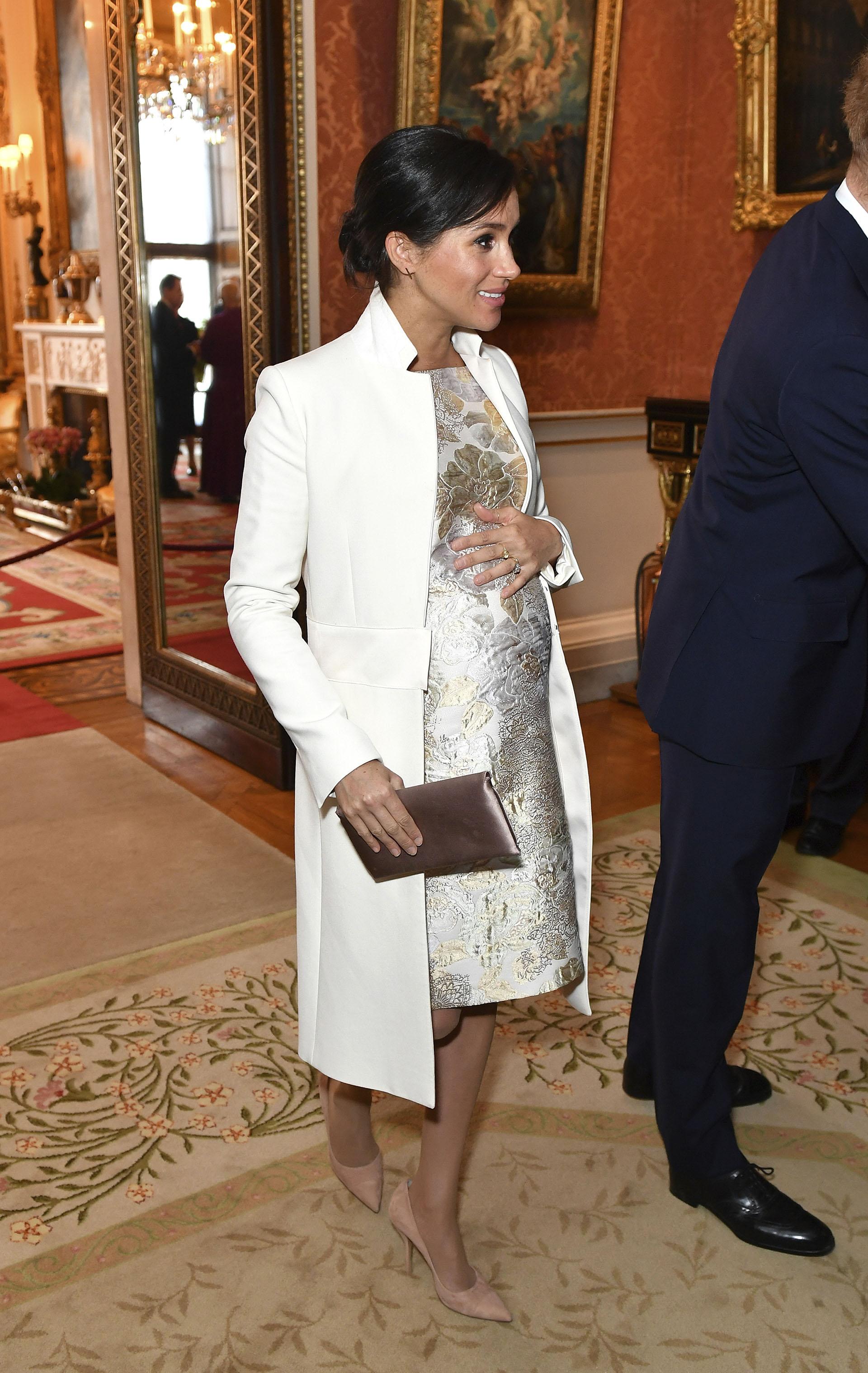 La duquesa de Sussex, asistió a una recepción en el Palacio de Buckingham, Londres, el martes 5 de marzo de 2019, para conmemorar el quincuagésimo aniversario de la investidura del Príncipe de Gales y lució un lookdeslumbrante vestido metálicoy un abrigo blanco de Amanda Wakeley (AP)
