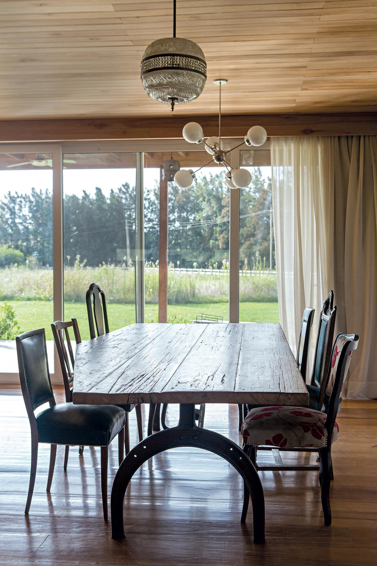Una mesa de campo rústica con sillas de diferentes estilos conforman el comedor.