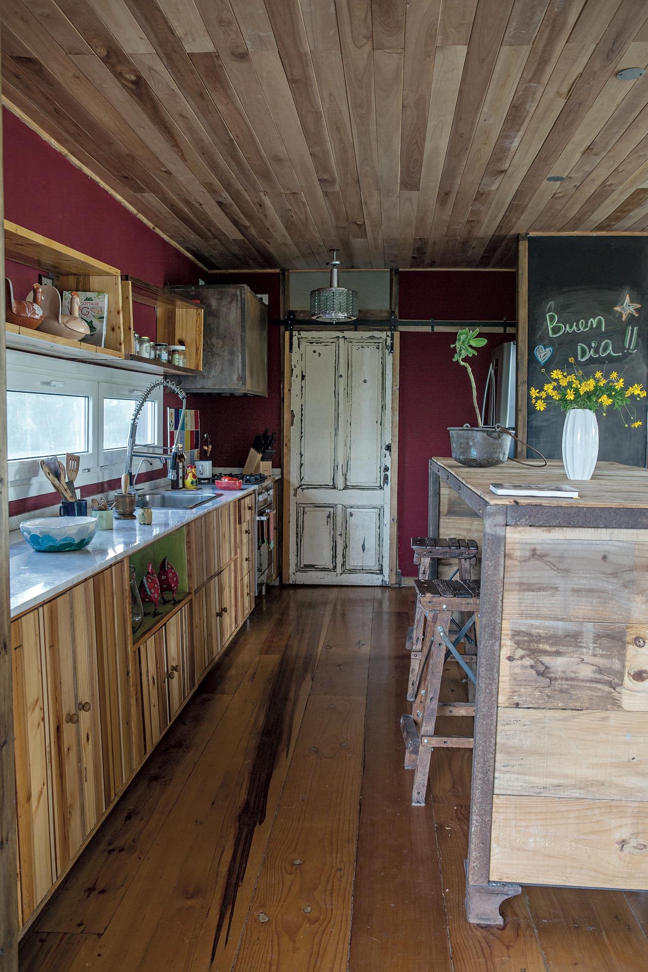 Paredes color bordó y mucha madera dan vida a esta cocina campestre.