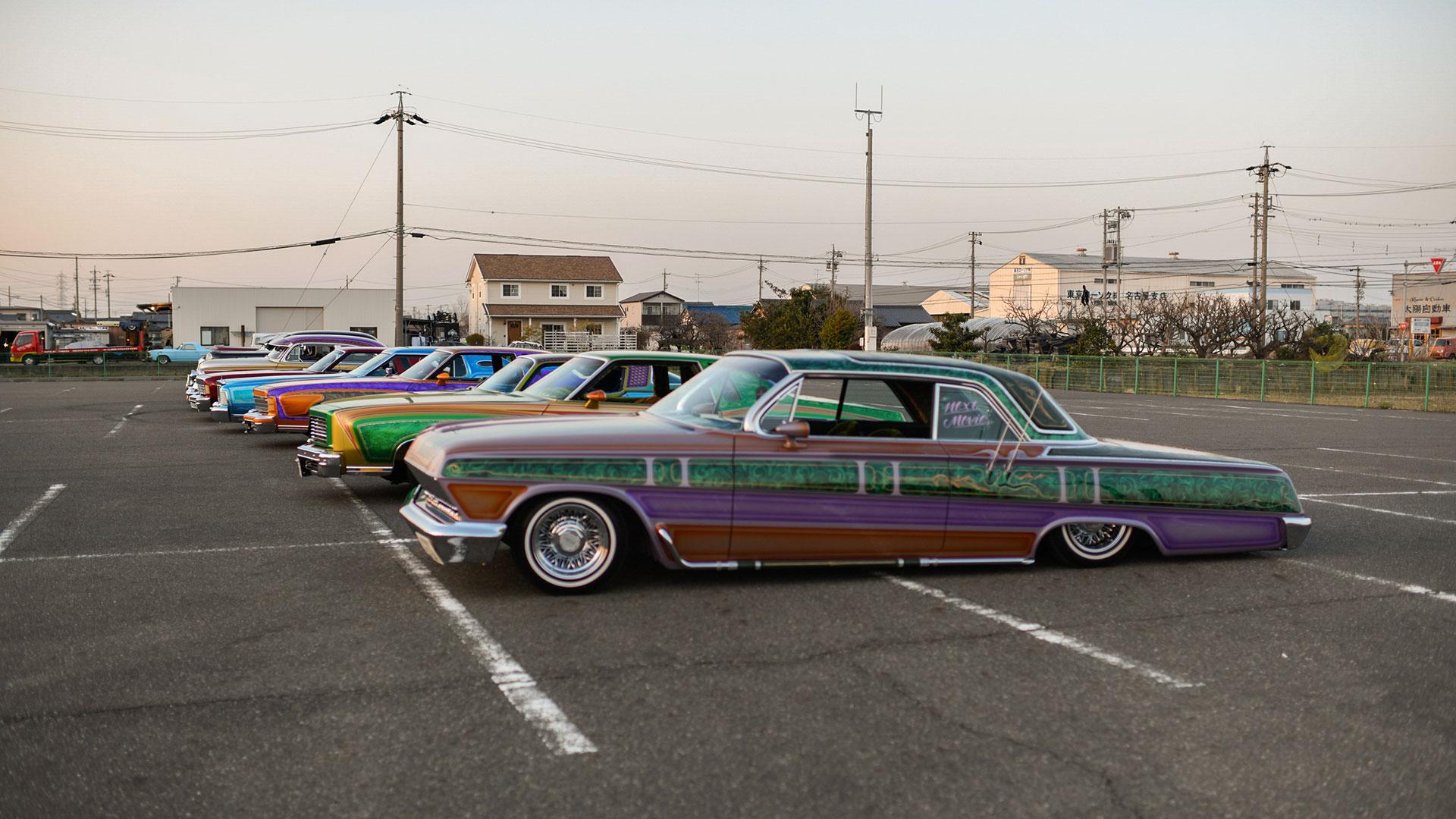 Un grupo de autos lowrider en un estacionamiento adyacente a la tienda de autos Cholos en Nagoya (The New York Times)