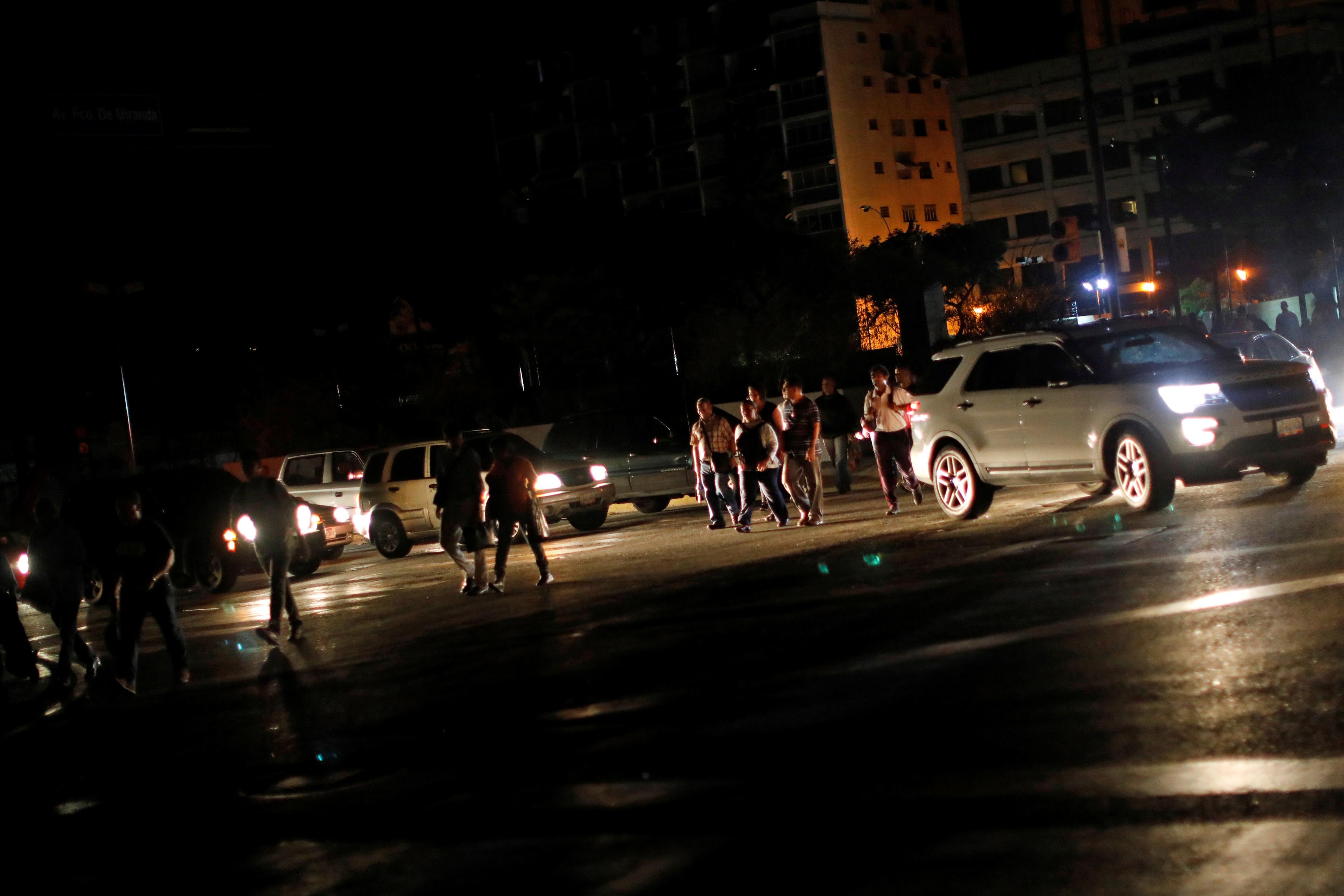 Personas caminando por una calle a oscuras en Caracas. (REUTERS/Carlos Jasso)